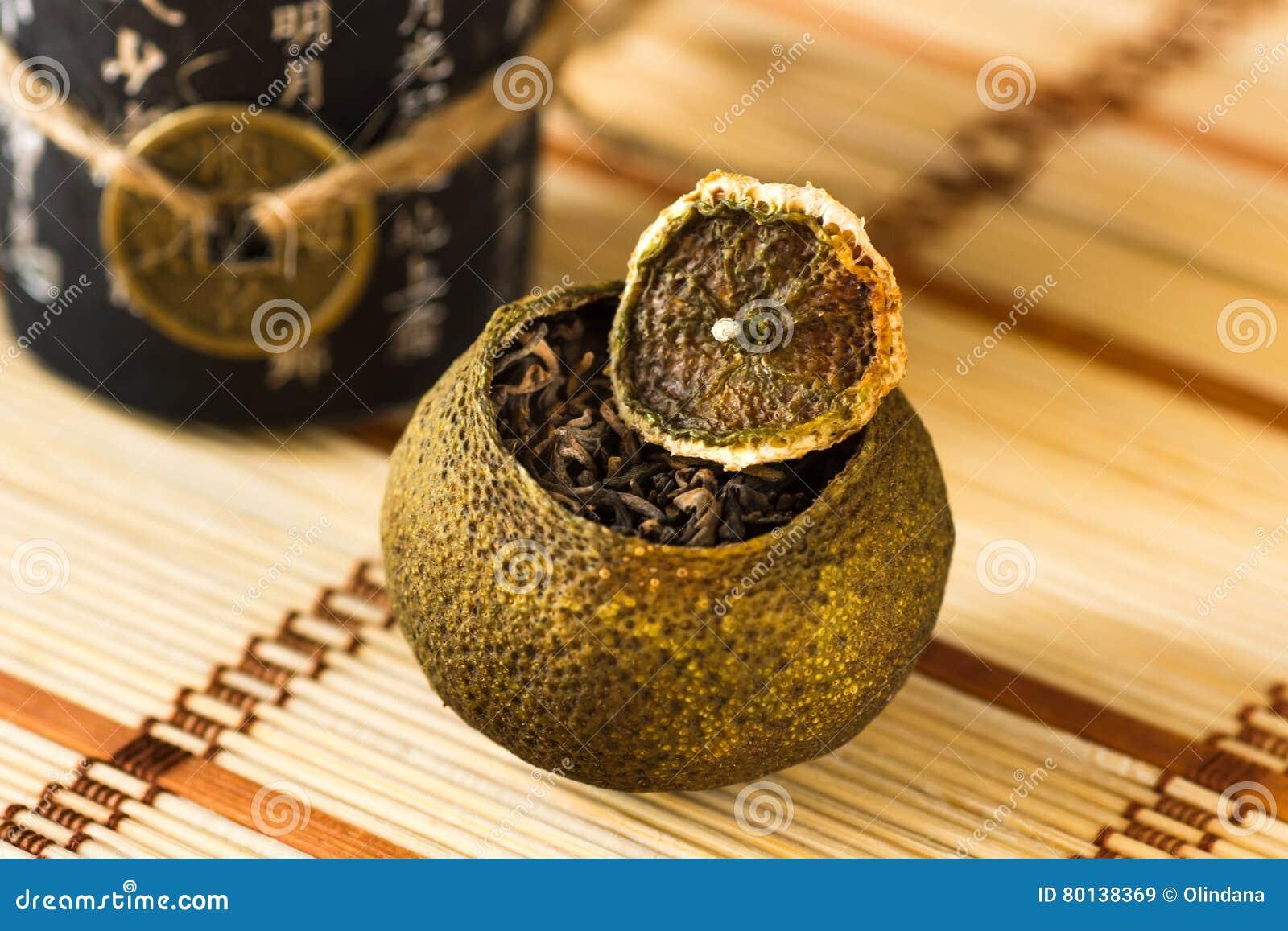 Åldrigt pu-erh te i en torr tangerinpeel på ett mattt sugrör för kinesisk stil, selektiv fokus