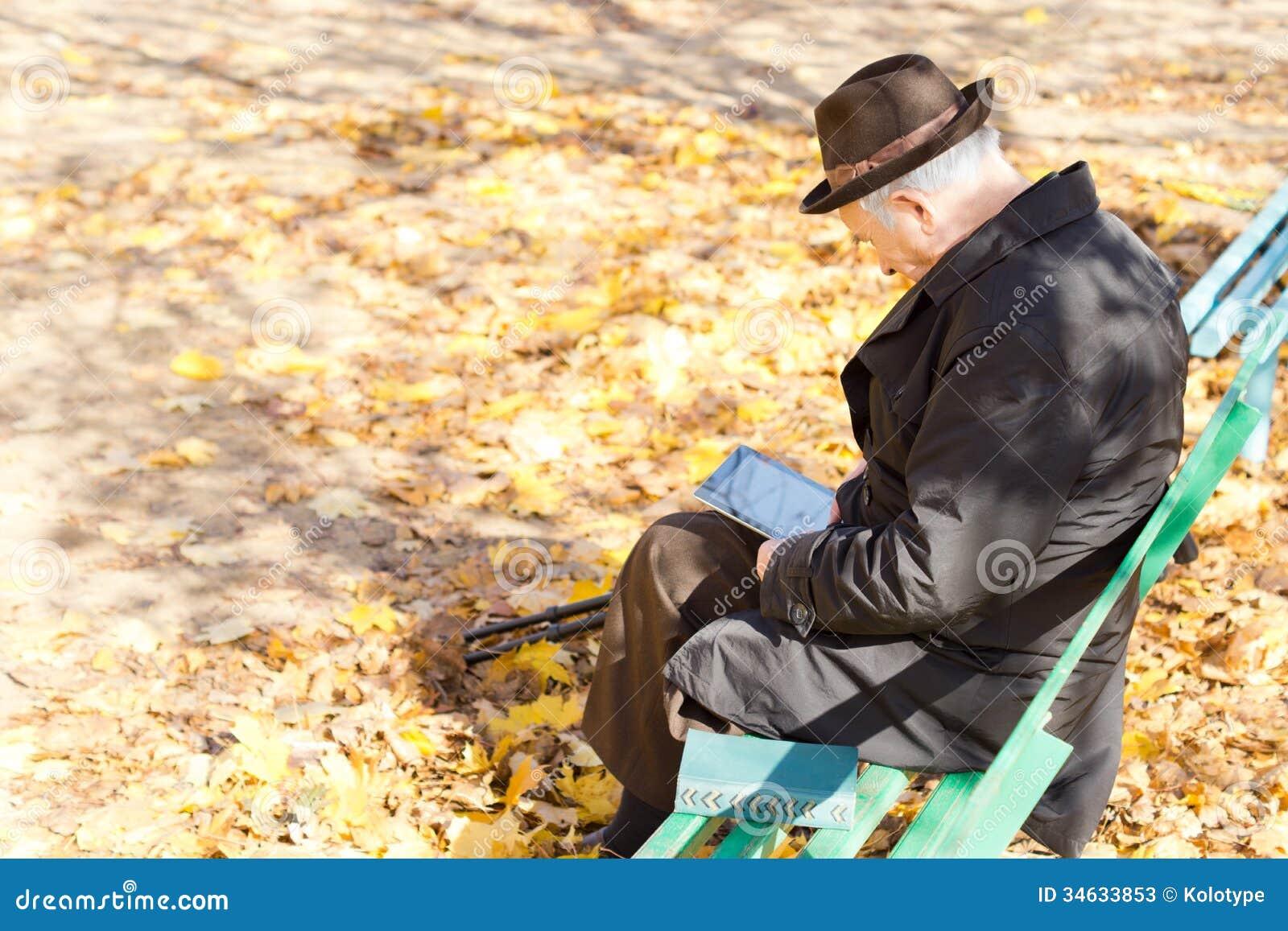 Åldring en lade benen på ryggen mansammanträdeläsning i parkera