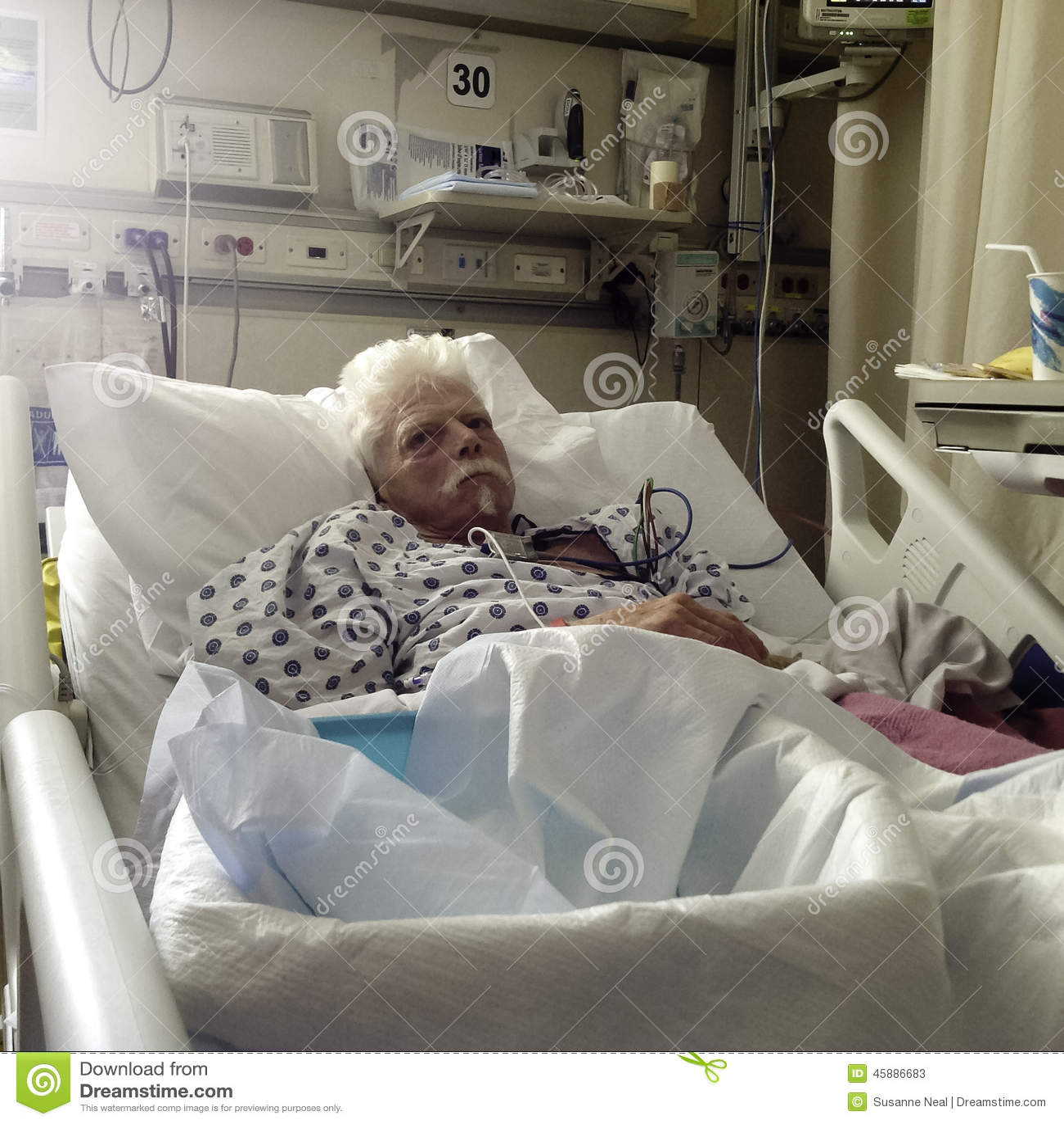Åldring vit haired manlig patient i sjukhussäng
