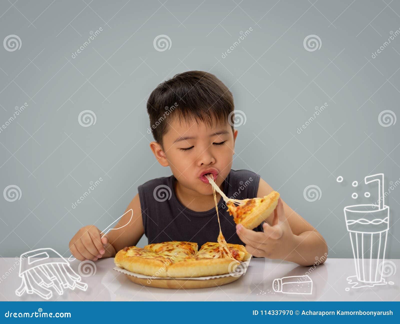 Årspojken för asiat 6-7 är lycklig till att äta pizza med varma wi för en ost