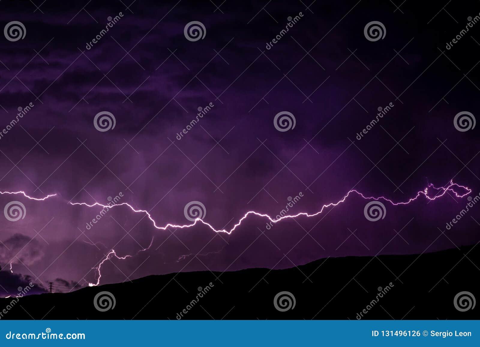 Åskvigg över bergen med det höga elektriska spänningstornet