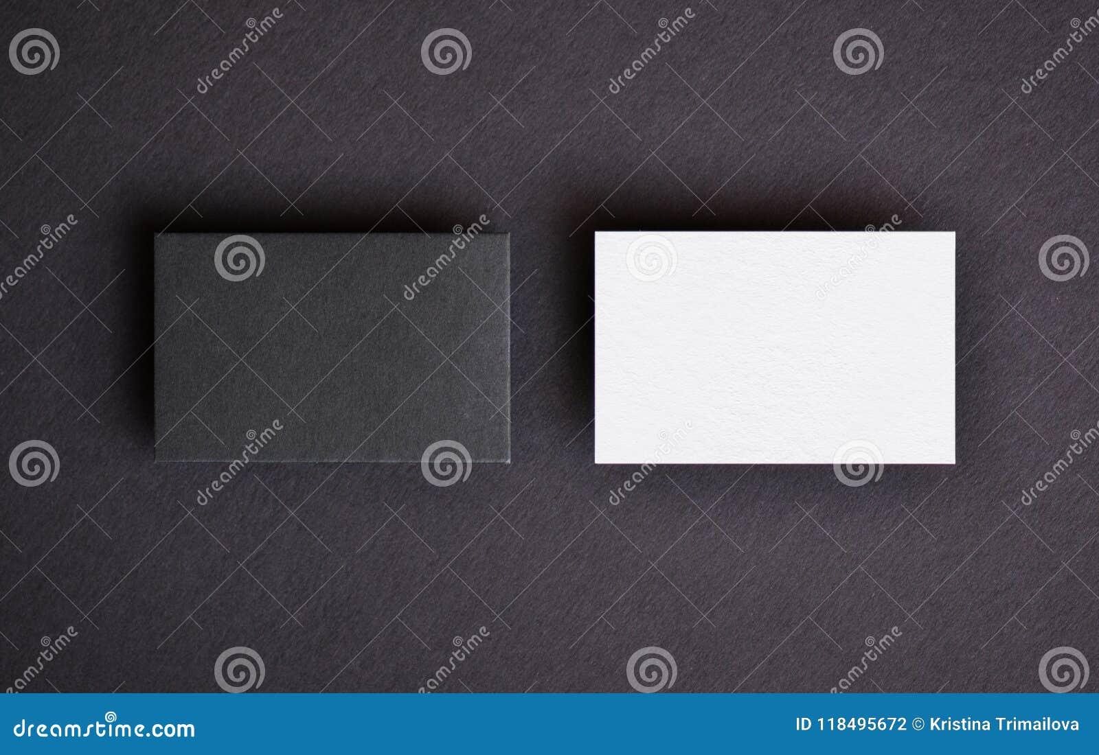 Åtlöje upp av två horisontalsvartvita affärskort på svart texturerad pappers- bakgrund Modellmall för