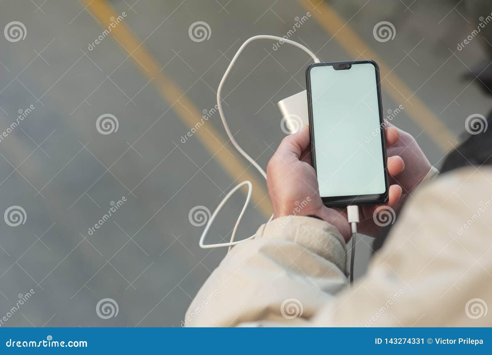 Åtlöje upp Smartphone med bärbar uppladdning i händerna av en man