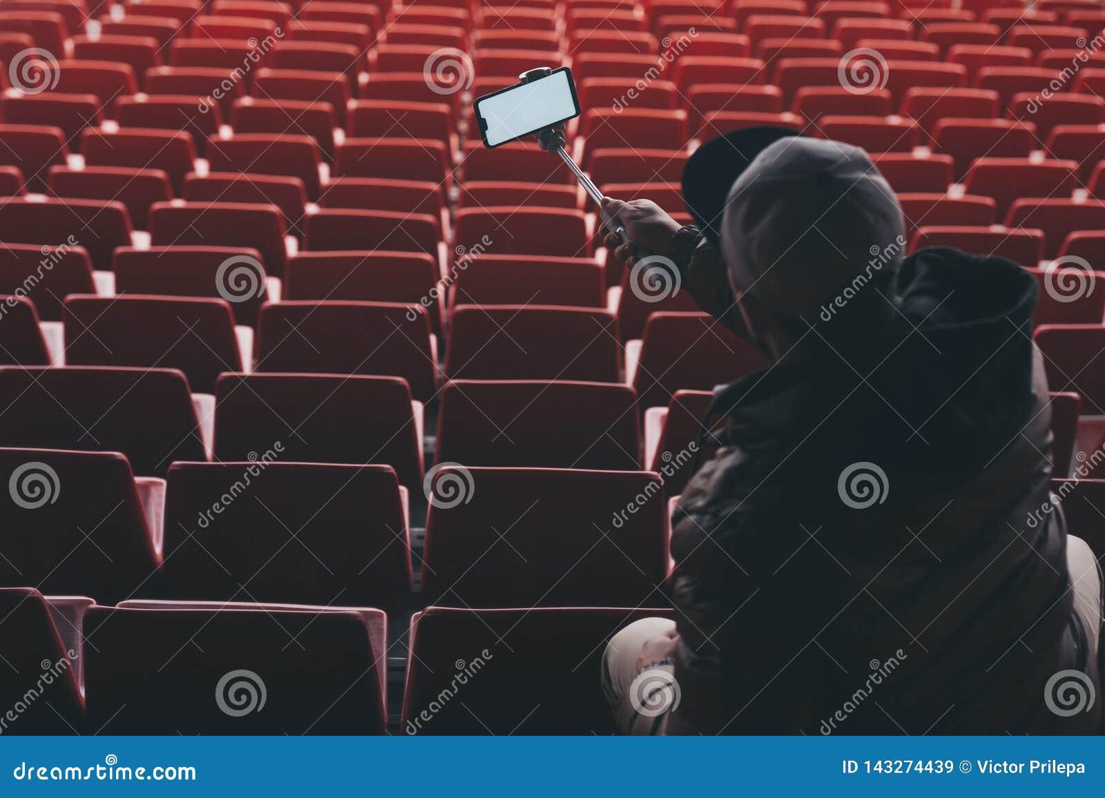 Åtlöje upp Smartphone med en selfiepinne i händerna av en man på bakgrunden av ställningarna Grabben tar en selfie på
