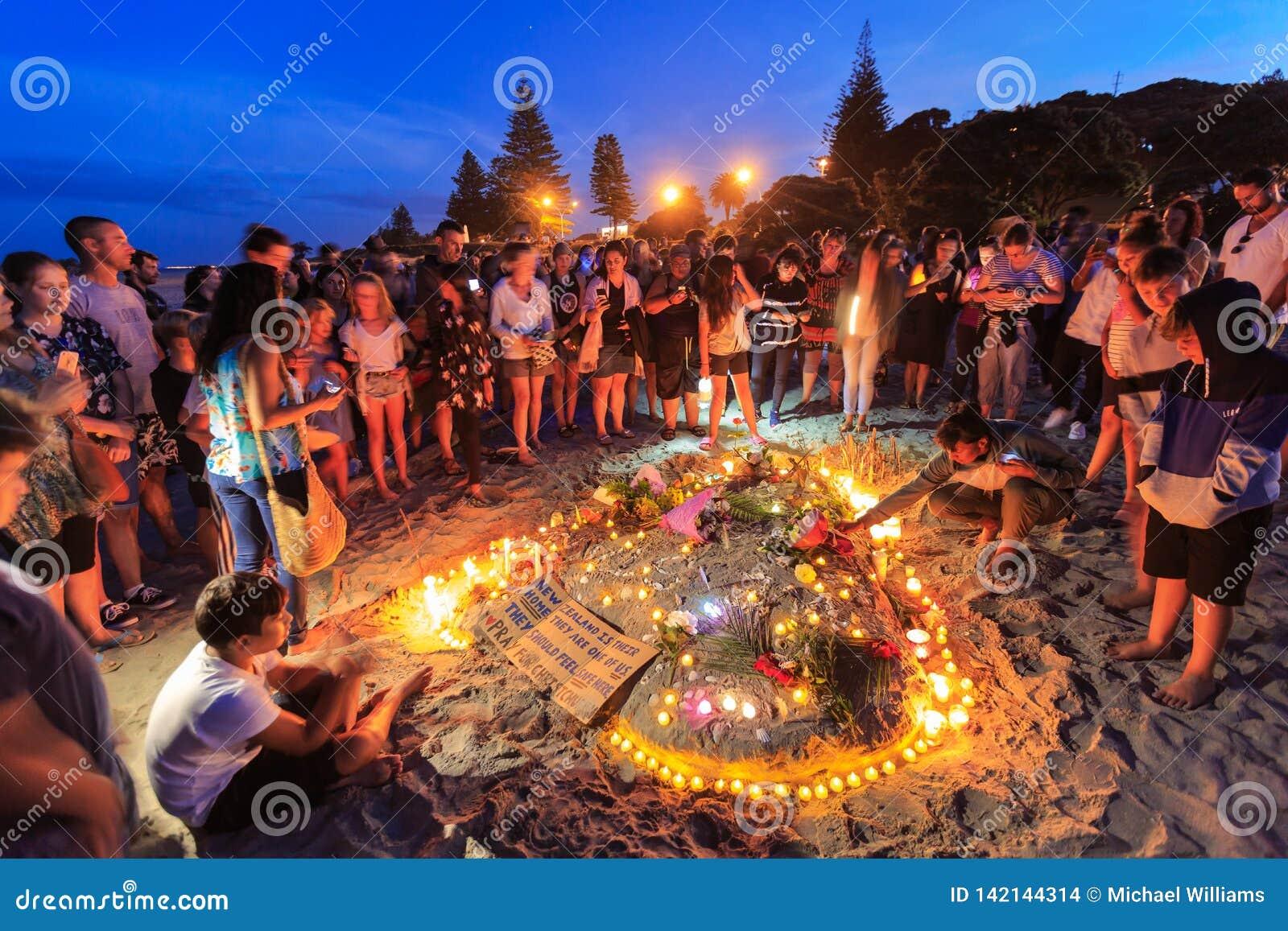 恐怖主义受害者的点蜡烛的海滩守夜,登上Maunganui,新西兰
