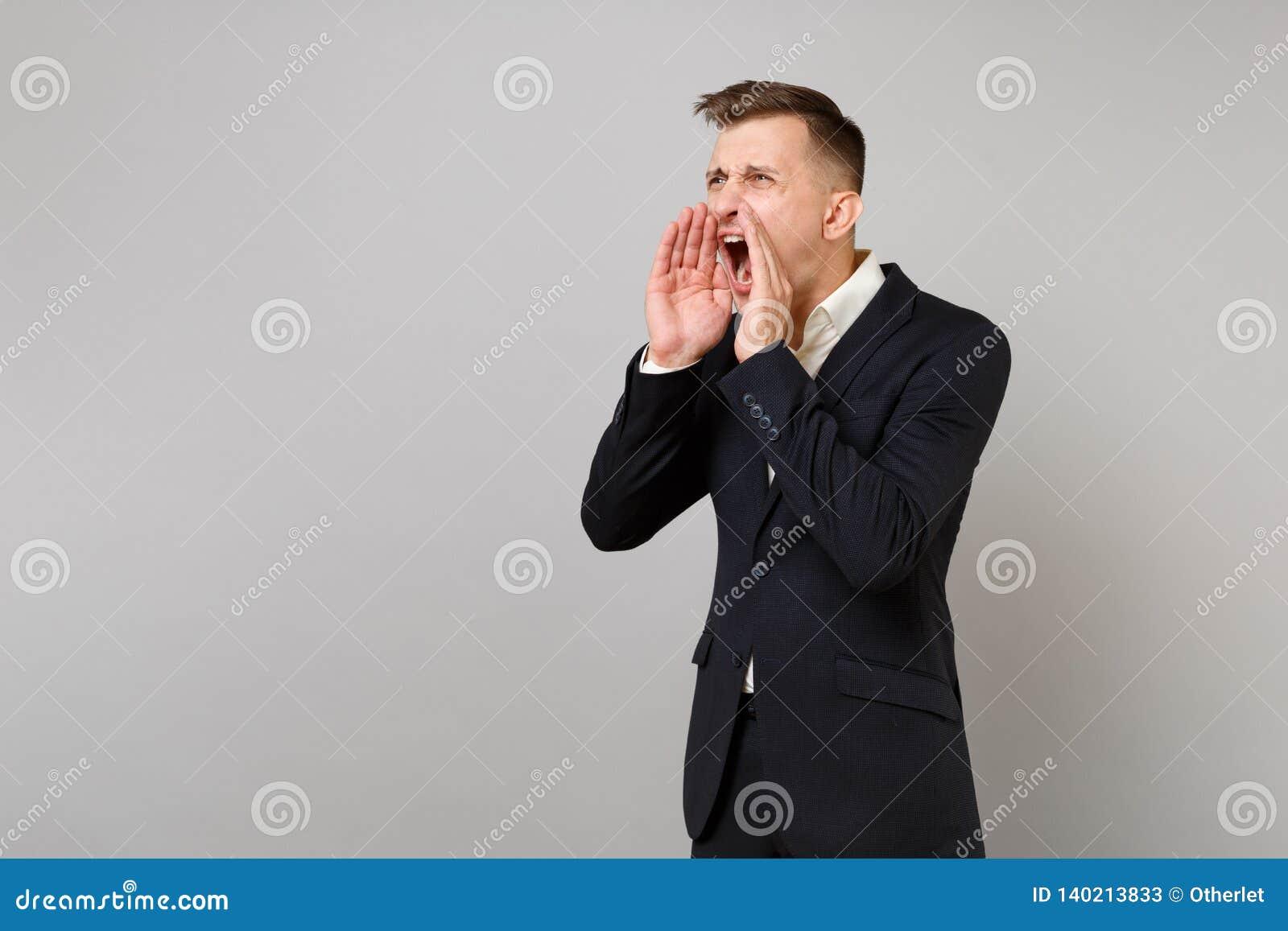 恼怒的年轻商人画象经典黑衣服衬衣的尖叫与手势隔绝在灰色墙壁上