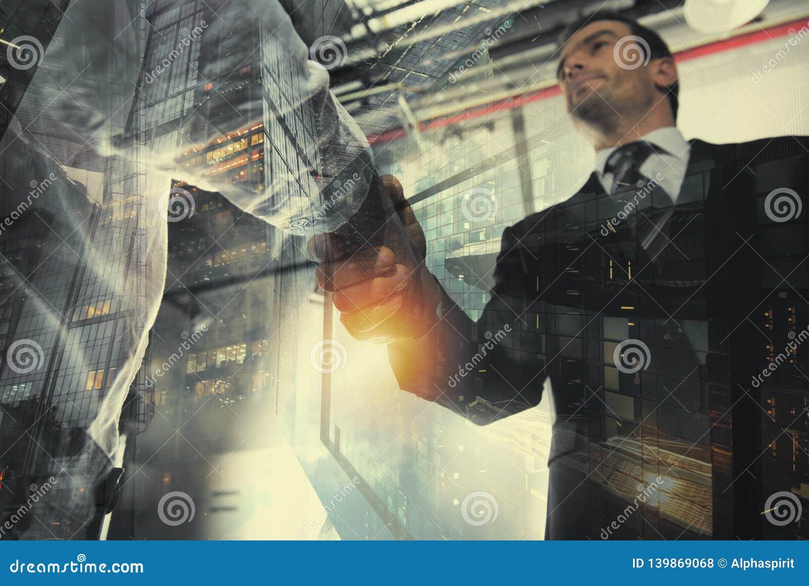 握手企业人在有网络作用的办公室 配合和合作的概念 两次曝光