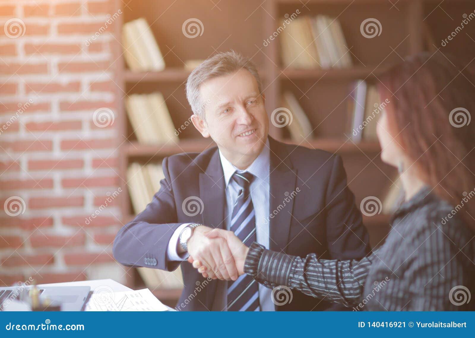 握手在桌面附近的商务伙伴在办公室