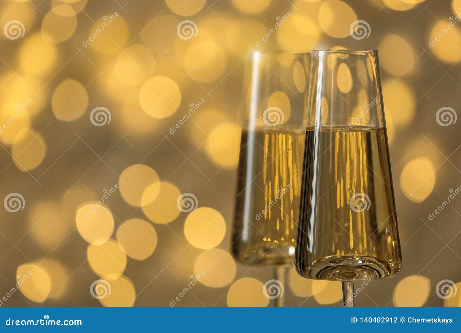 杯反对被弄脏的彩色小灯的泡沫腾涌的香槟