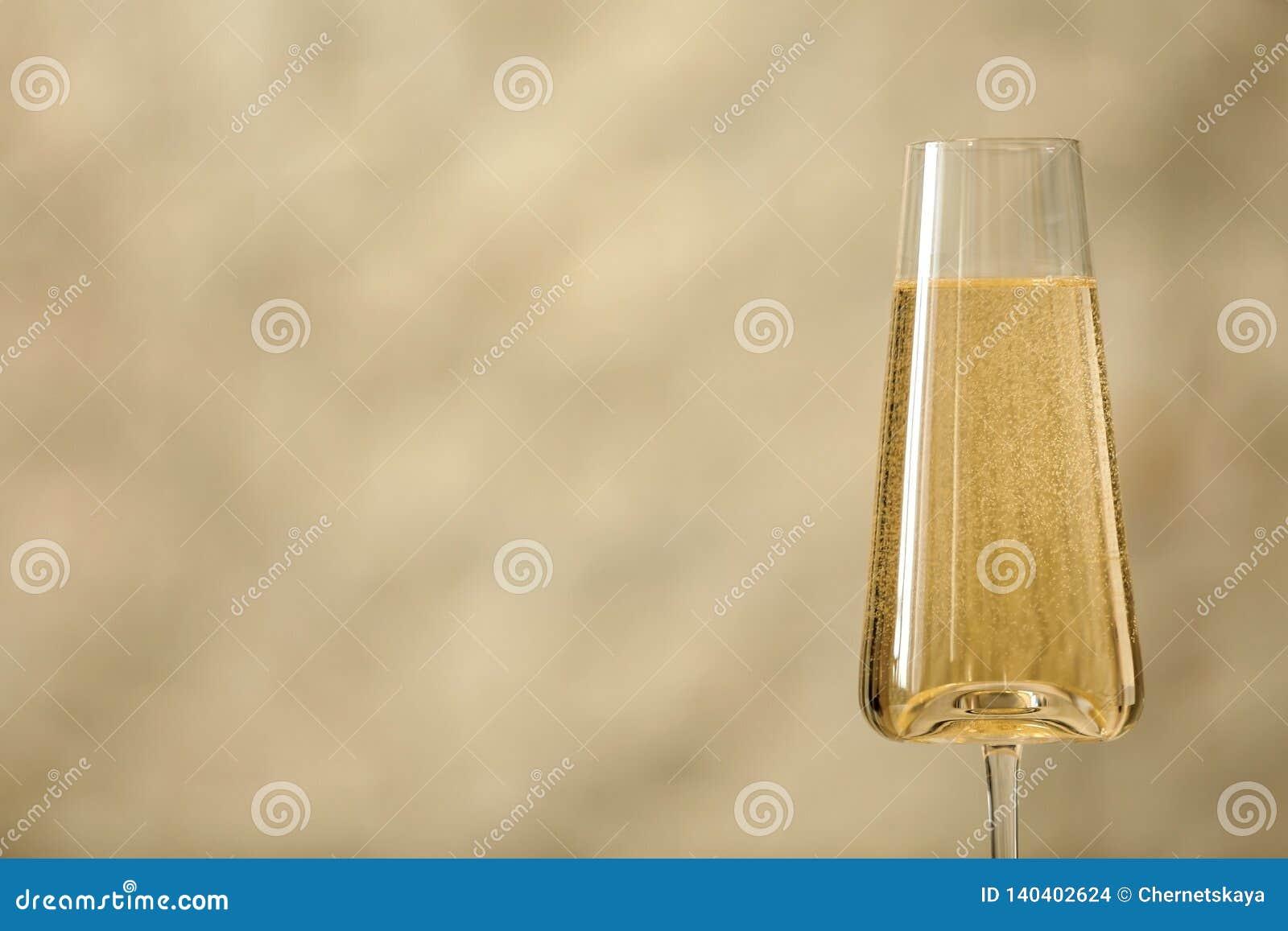 杯反对轻的背景的泡沫腾涌的香槟