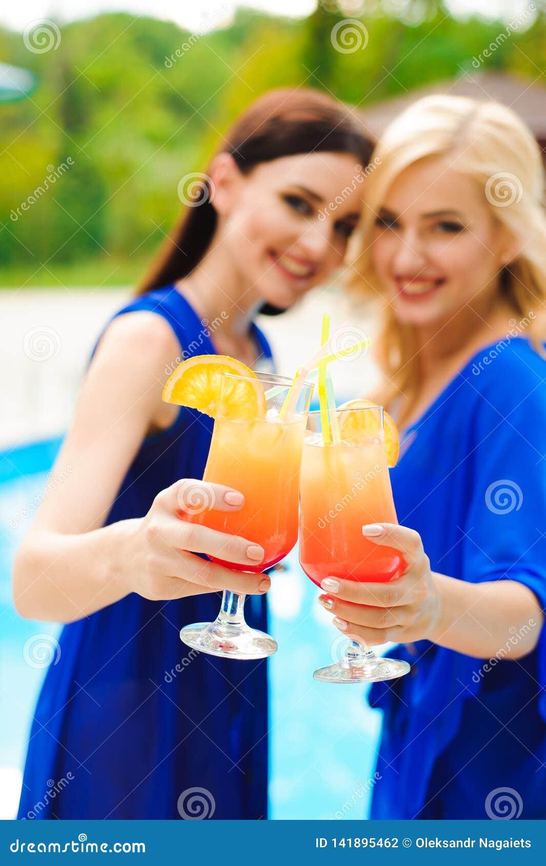 比基尼泳装的美丽的性感的妇女喝鸡尾酒一会儿的放松在游泳场