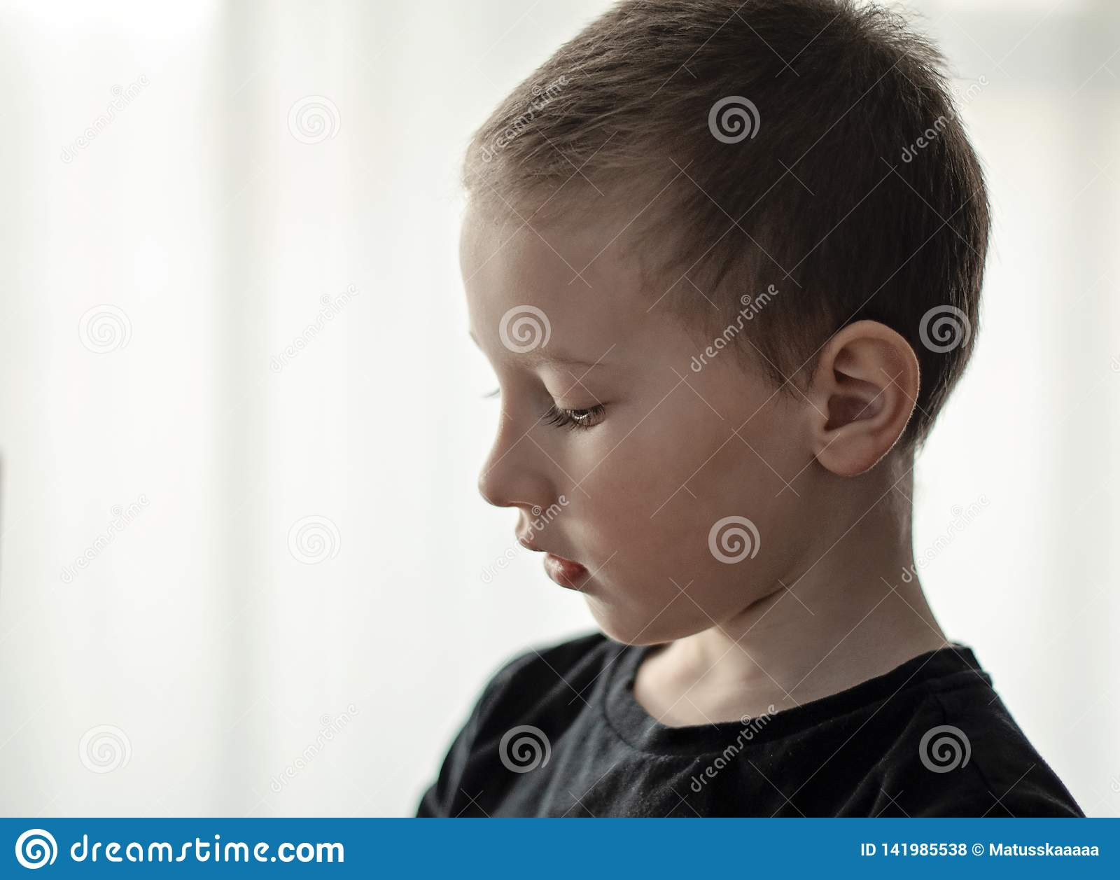 沮丧的年轻幼儿园男孩特写镜头画象认为黑的T恤杉的看下来和 有哀伤的面孔的不快乐的单独孩子