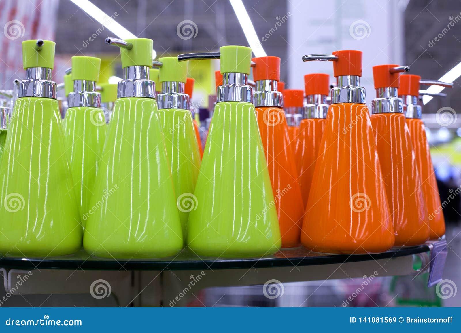 液体皂、卫生间陶瓷辅助部件以绿色和橘黄色的浴皂盒分配器在玻璃搁置在商店关闭