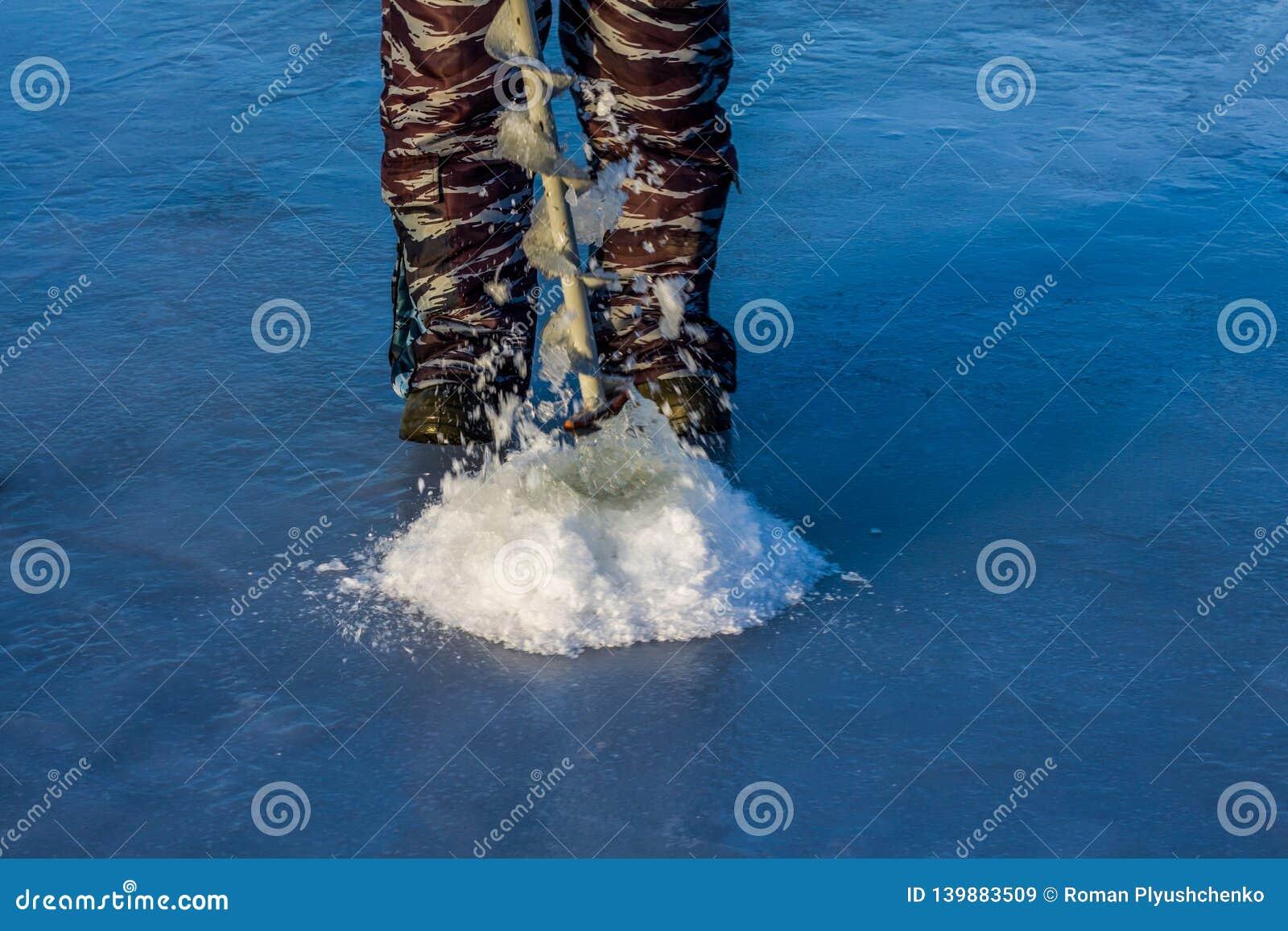 渔夫钻井在冰的一个孔