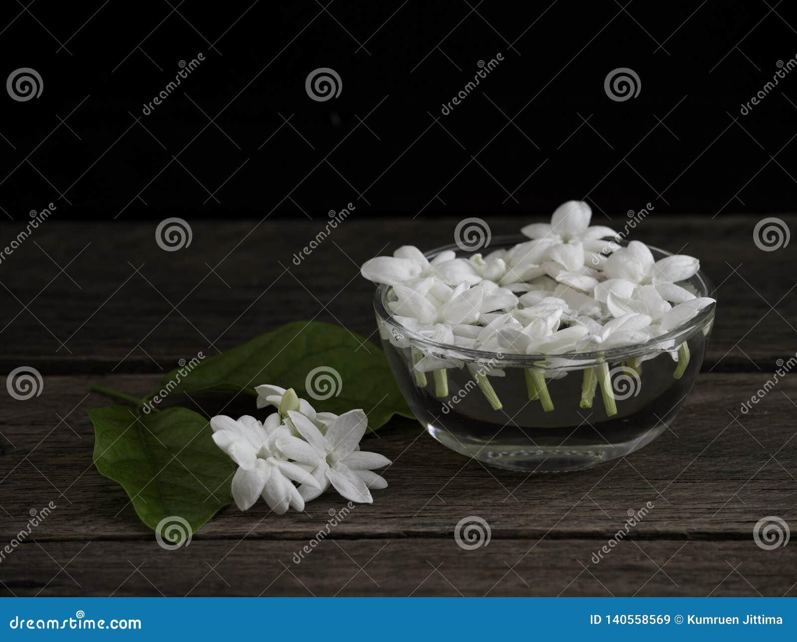 漂浮在木背景的清楚的玻璃的茉莉花