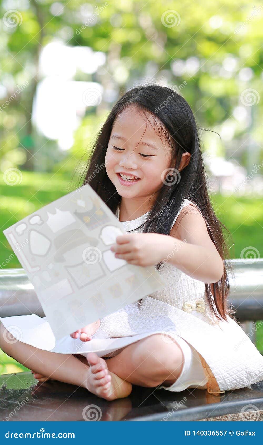 演奏贴纸的愉快的矮小的亚裔儿童女孩在绿色公园