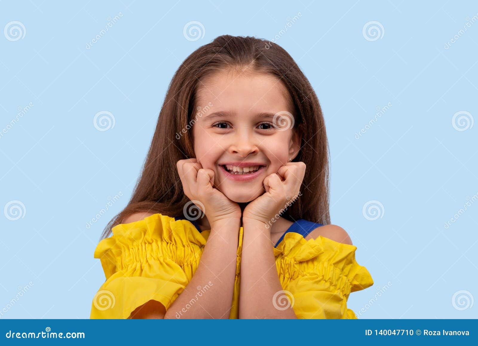 演播室射击了女孩穿戴了在蓝色背景的黄色sundress 她甜甜地微笑与她的拳头对她的面颊