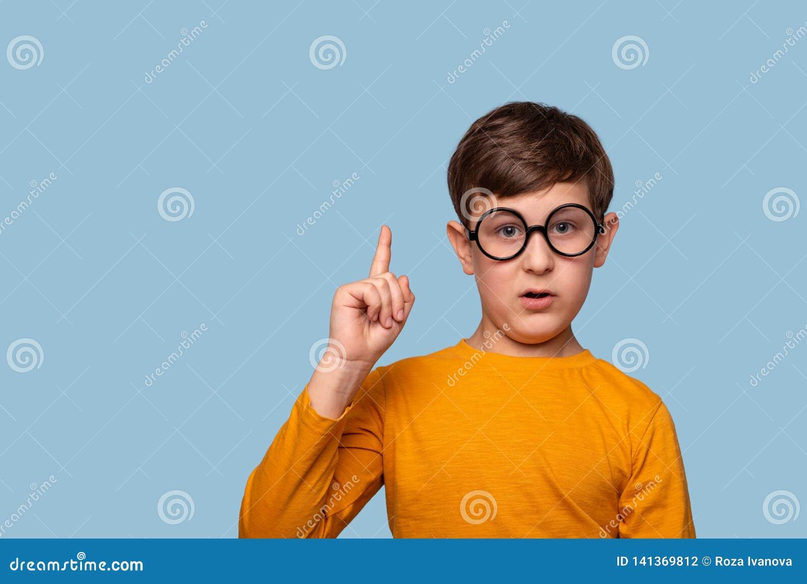 演播室被射击证明某事的圆的玻璃的一个滑稽的男孩通过举他的食指,隔绝在与拷贝空间的蓝色