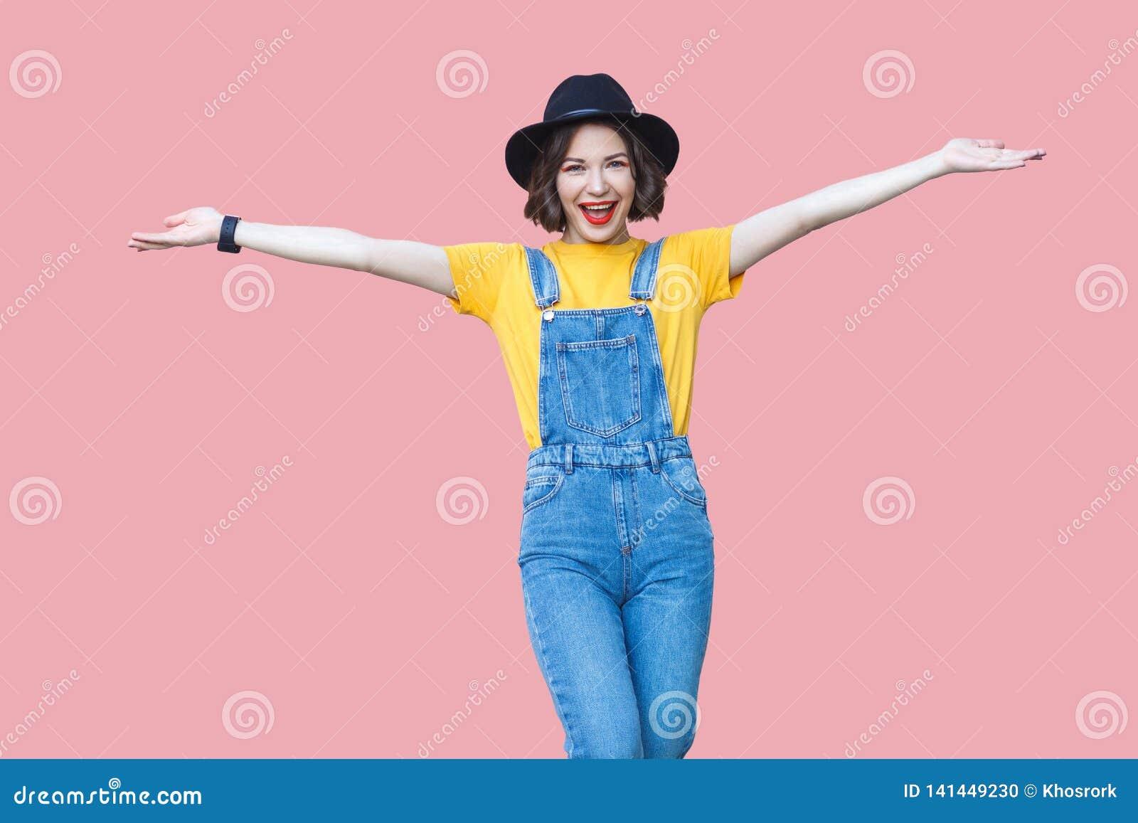 激动的美丽的年轻女人画象黄色T恤杉的,蓝色牛仔布总体,构成,与被举的胳膊的黑帽会议身分和