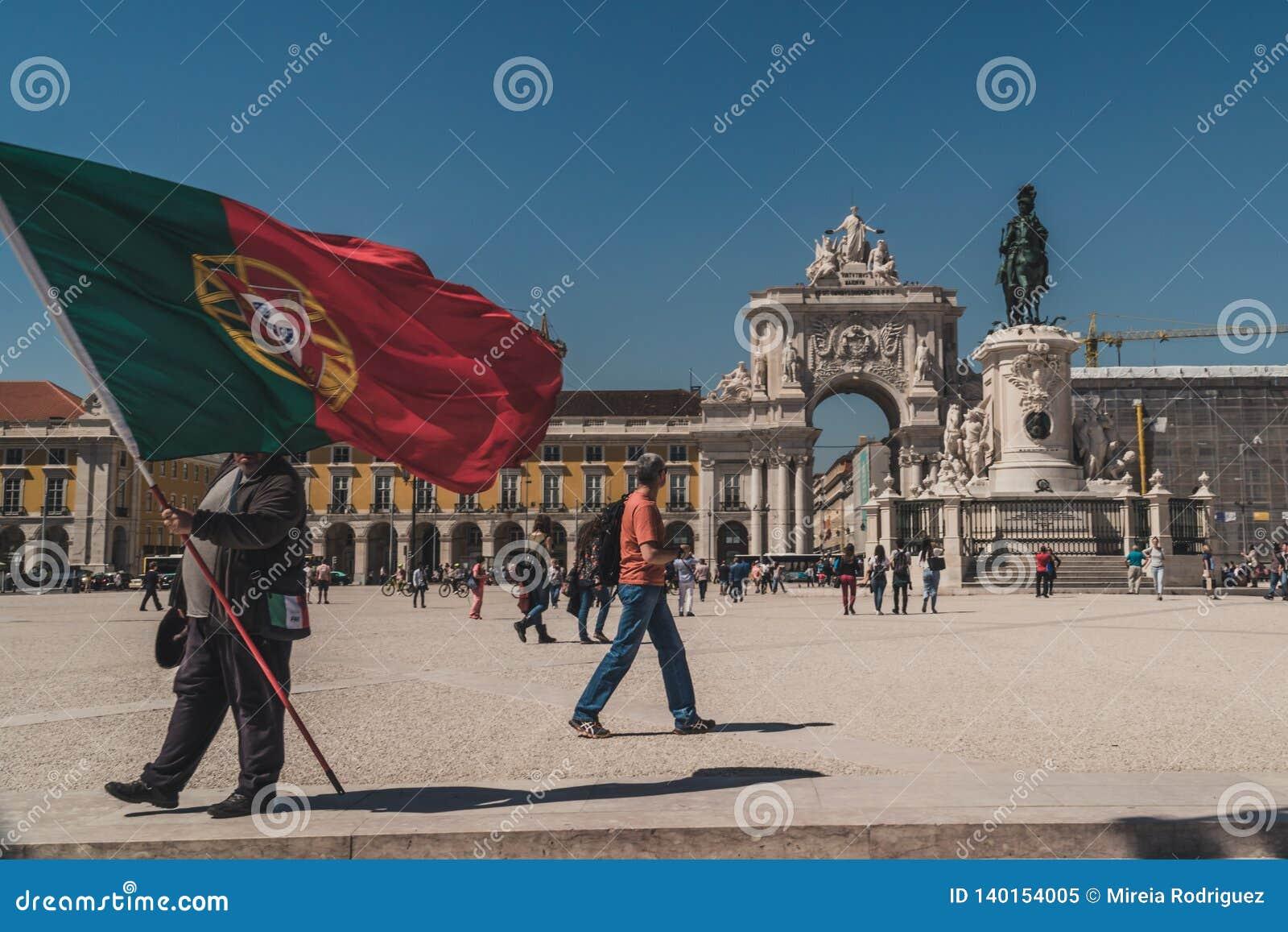 某人在街市里斯本拿着葡萄牙的一面巨型旗子Praça的做Comércio商务正方形