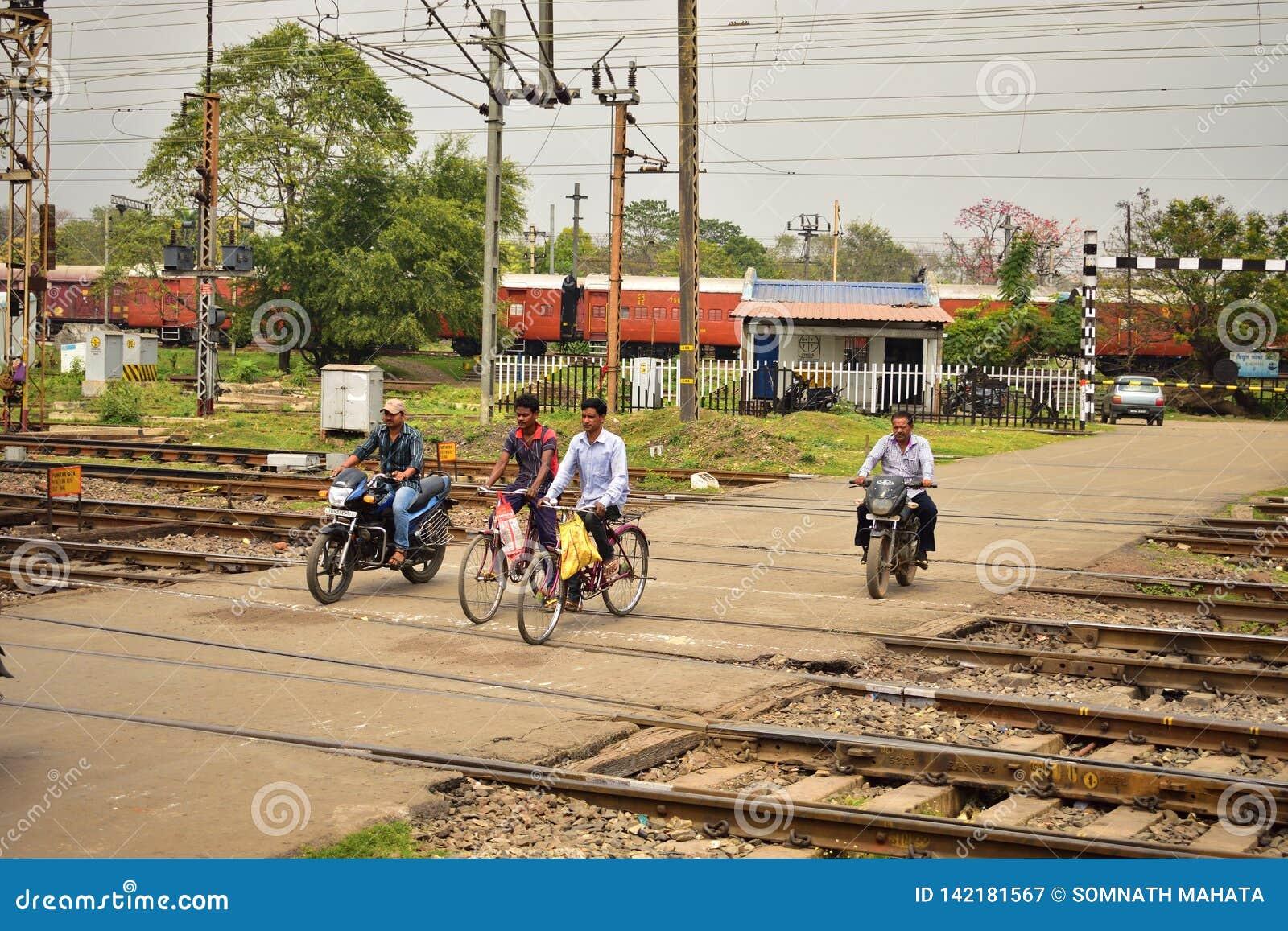 某些人在Tatanagar火车站附近横渡铁路交叉在摩托车或在周期