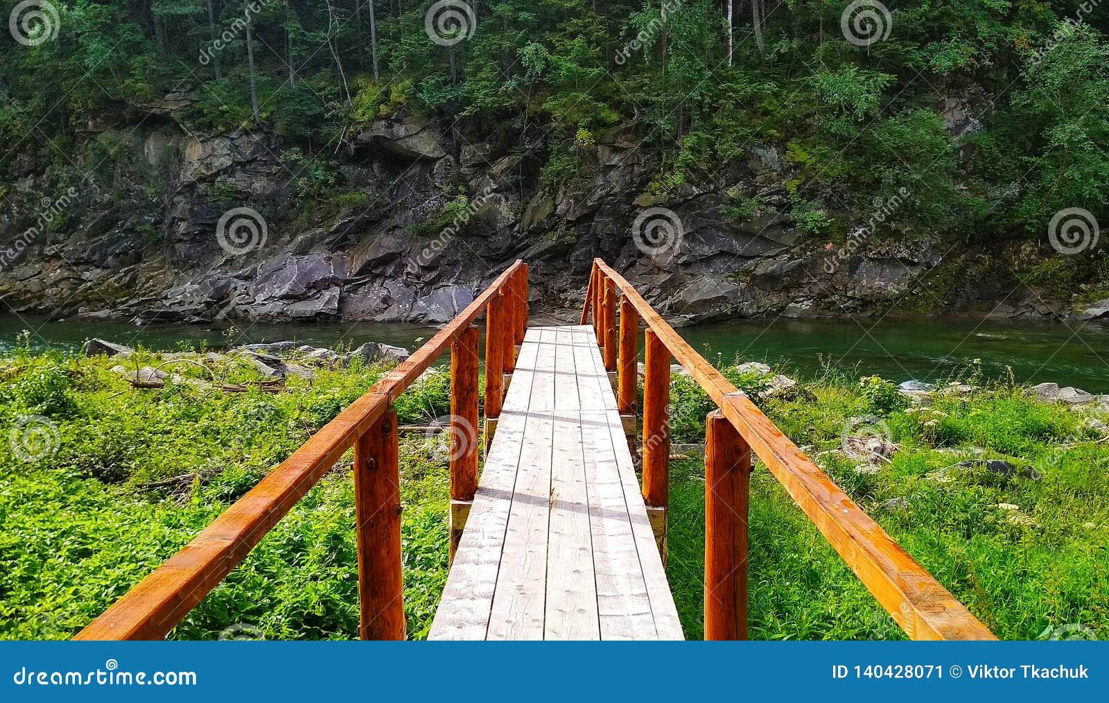 木桥在有岩石的山河在背景中