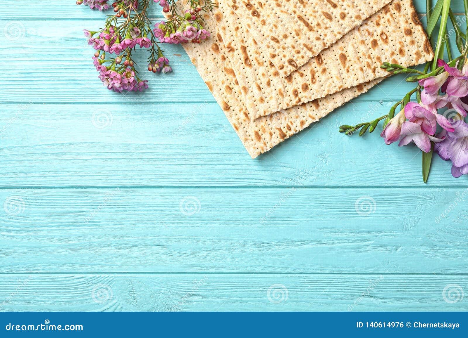 未发酵的面包和花的平的被放置的构成在木背景 逾越节Pesach Seder