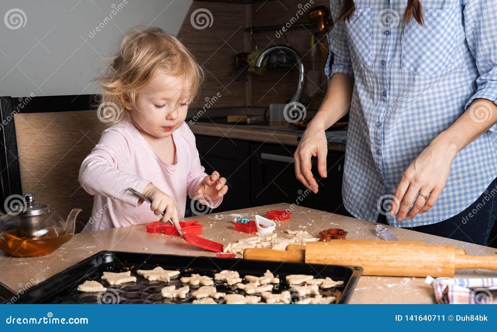 有一个小女儿婴孩的妈妈在厨房里准备曲奇饼 场面从家庭的现实