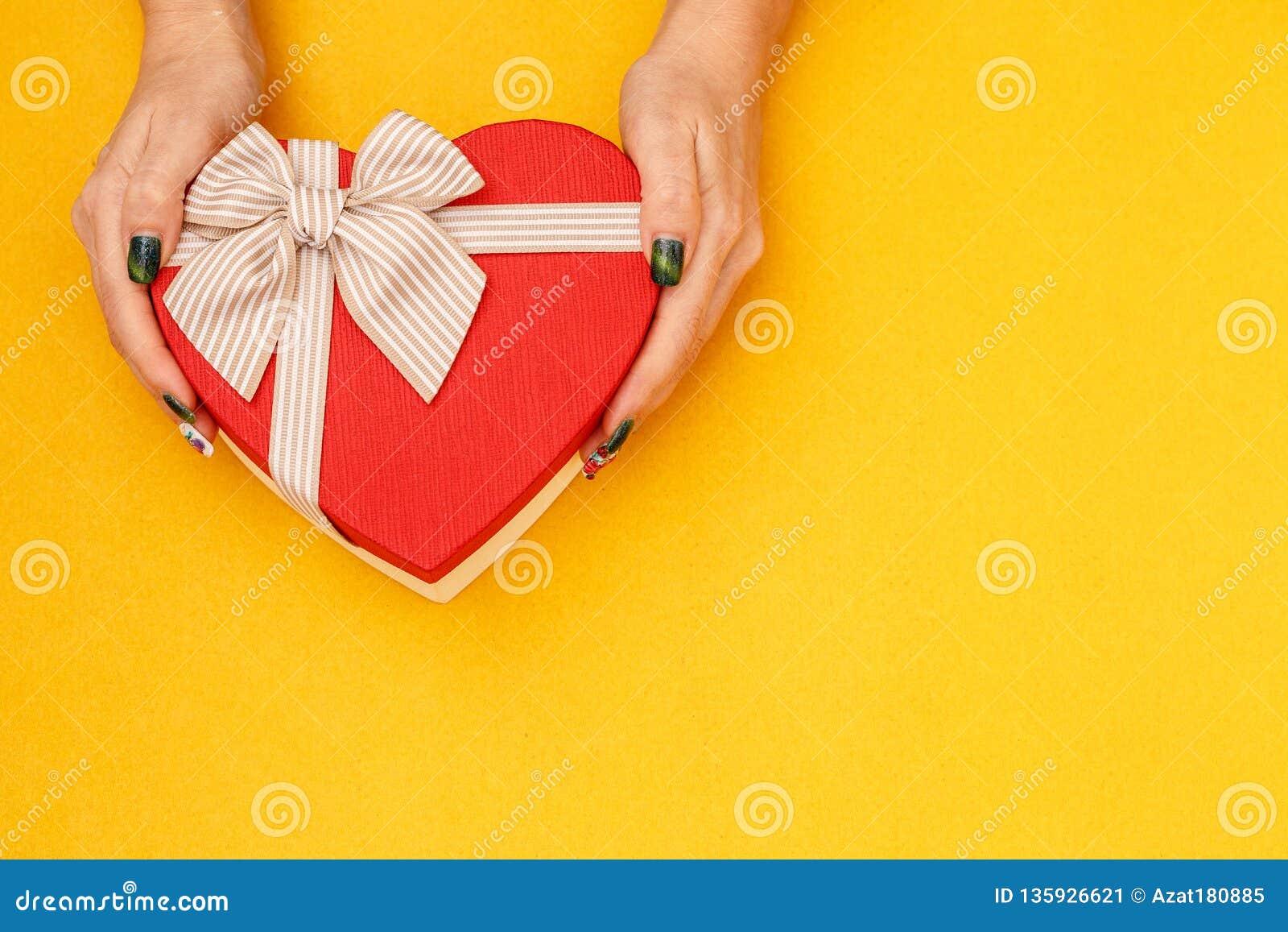 有一条丝带的礼物盒在女性手上 概念适用于爱情故事、生日和瓦伦蒂