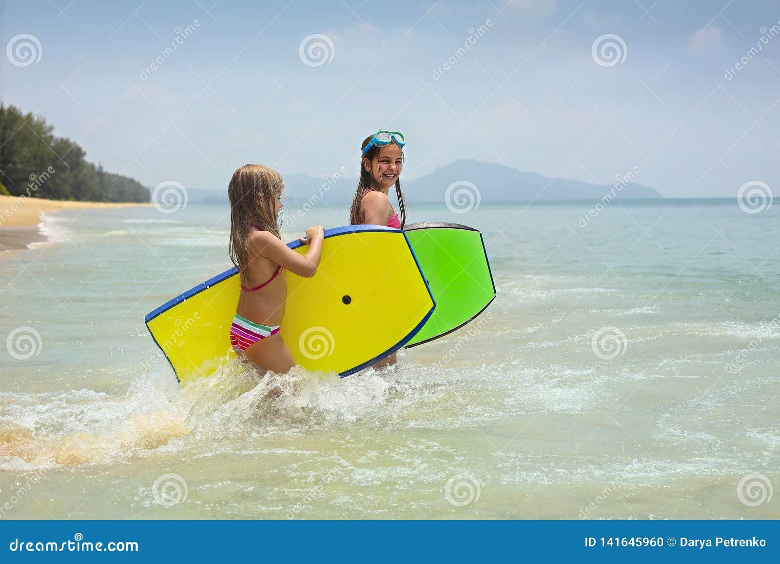 有使用在热带海洋海滩的水橇板的女孩 夏天冲浪者孩子的水乐趣