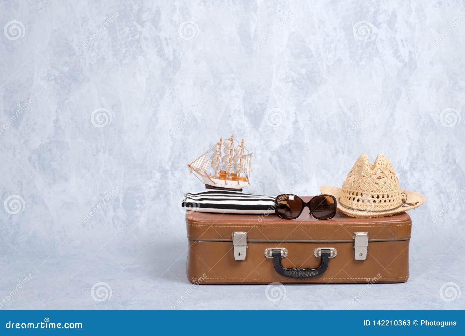 有夏天海洋辅助部件的古板的皮革旅行包:玻璃,秸杆海滩帽子,在灰色背景的玩具风船 钞票