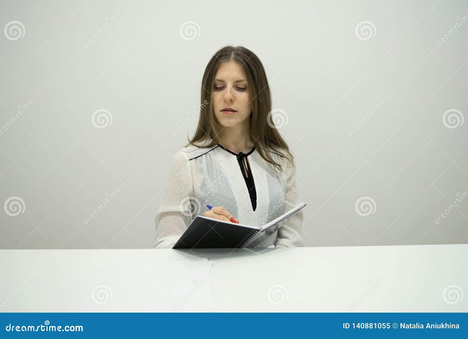 有她的头发的年轻深色的女孩直接坐在与一个笔记本的桌上在她的手上