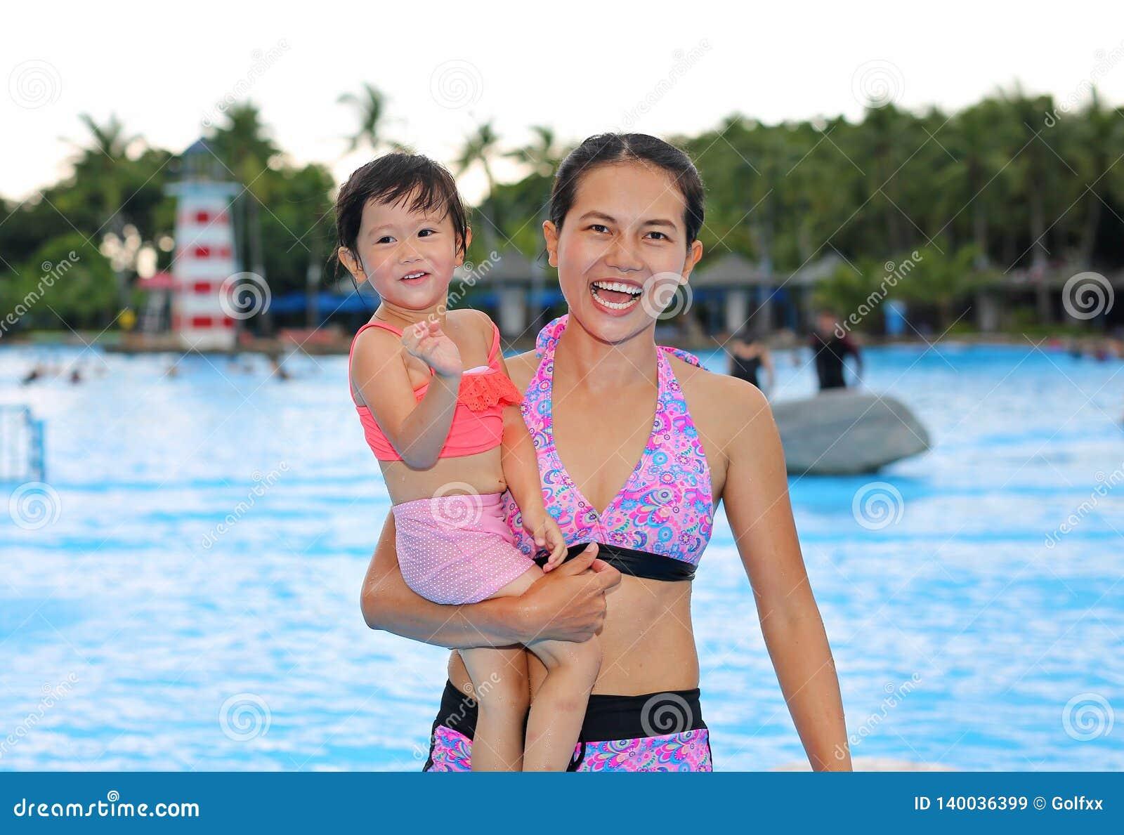 有她的母亲的俏丽的女孩户外游泳场的
