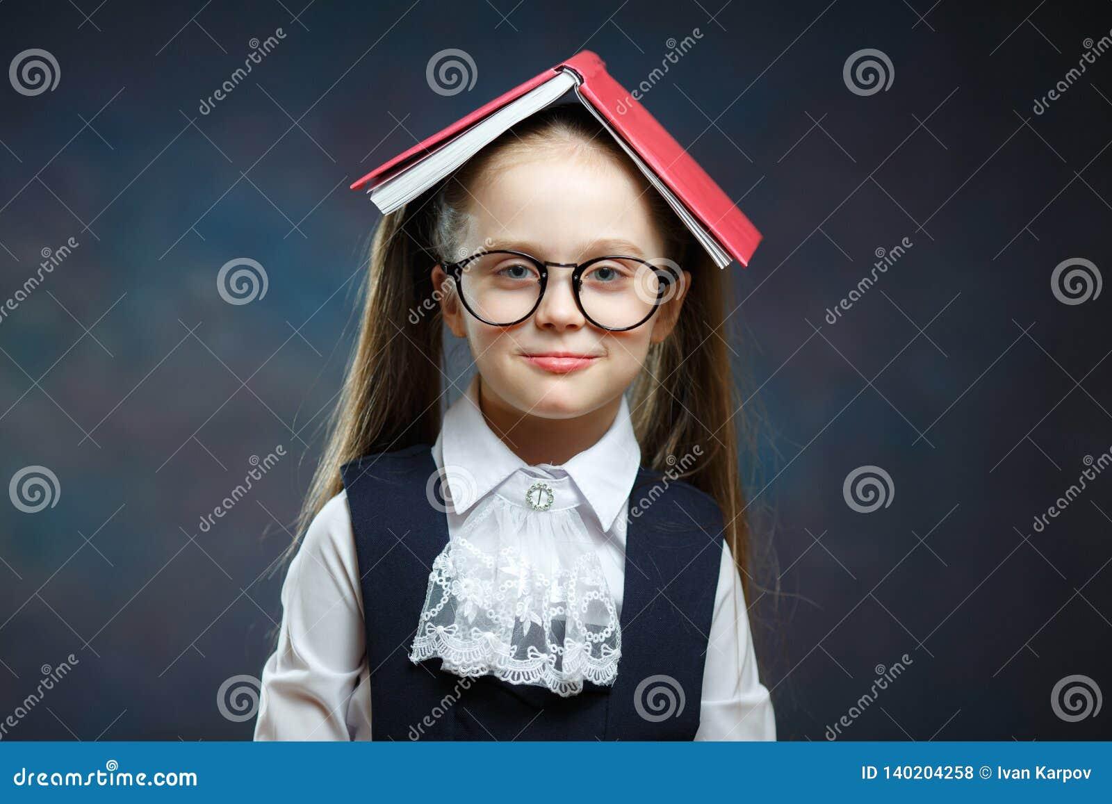 有开放书的逗人喜爱的女小学生呼喊盖子头