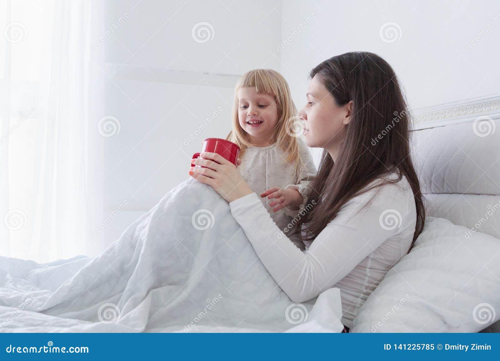有喝一些茶的女儿的年轻母亲,当坐在床上在白色卧室时