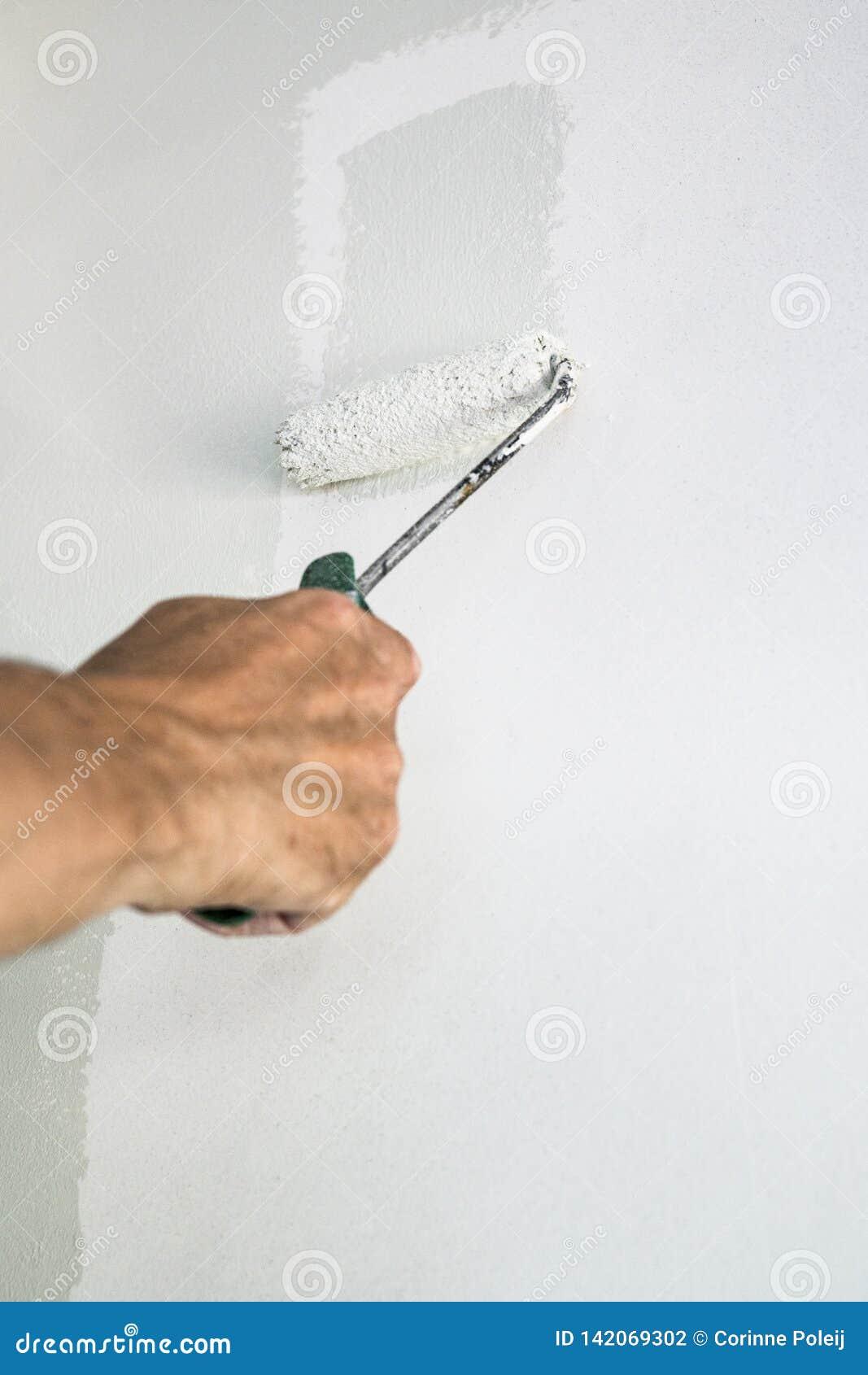 有漆滚筒和灰色油漆的手