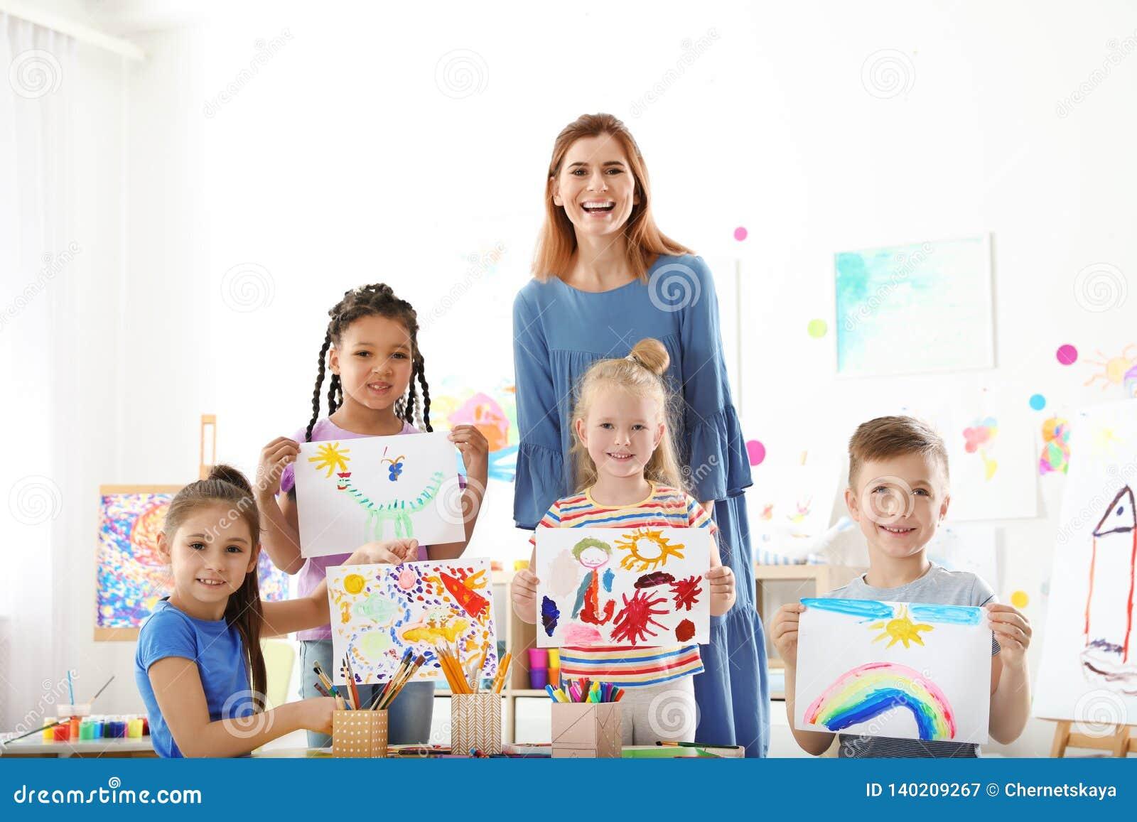 有显示他们的绘画的老师的逗人喜爱的小孩