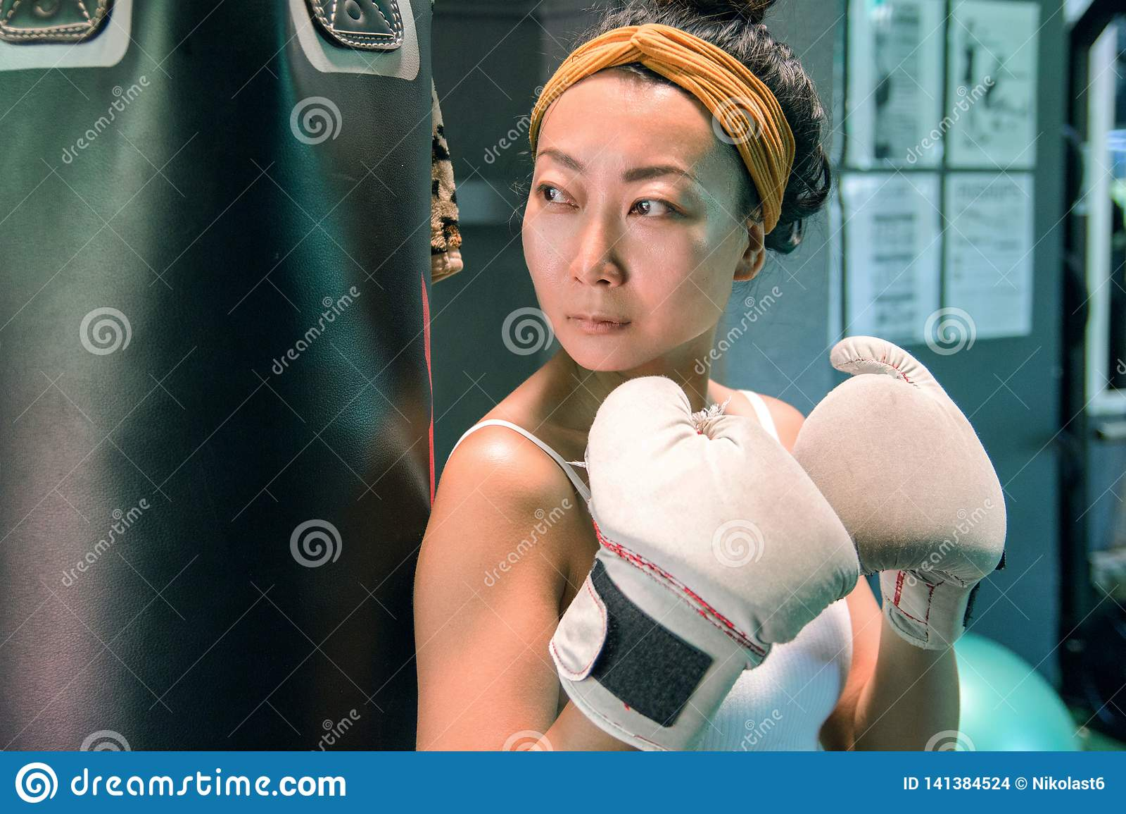 有站立在健身房的一个梨附近的白色拳击手套的美丽的亚裔女孩
