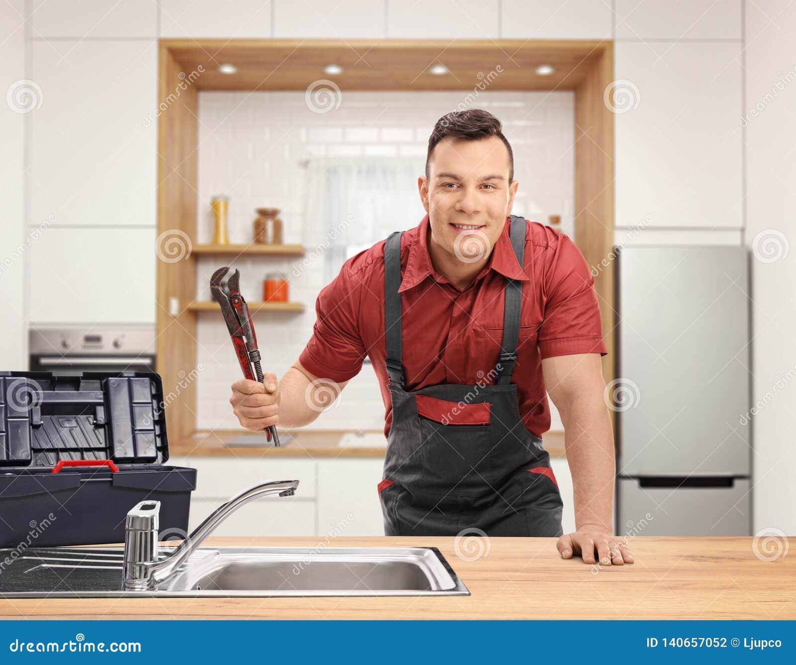 有管扳手的水管工和在一个水槽后的一个工具箱身分在厨房里