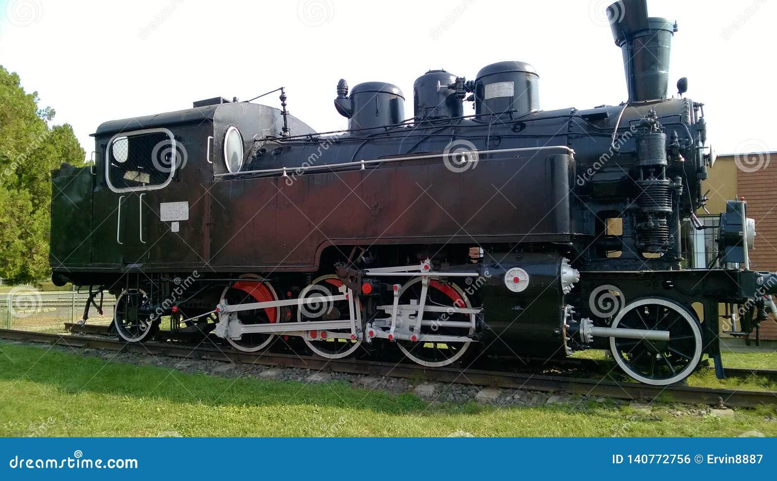 有白色轮子的蒸汽机车 在路轨的减速火箭的机车 黑色机车