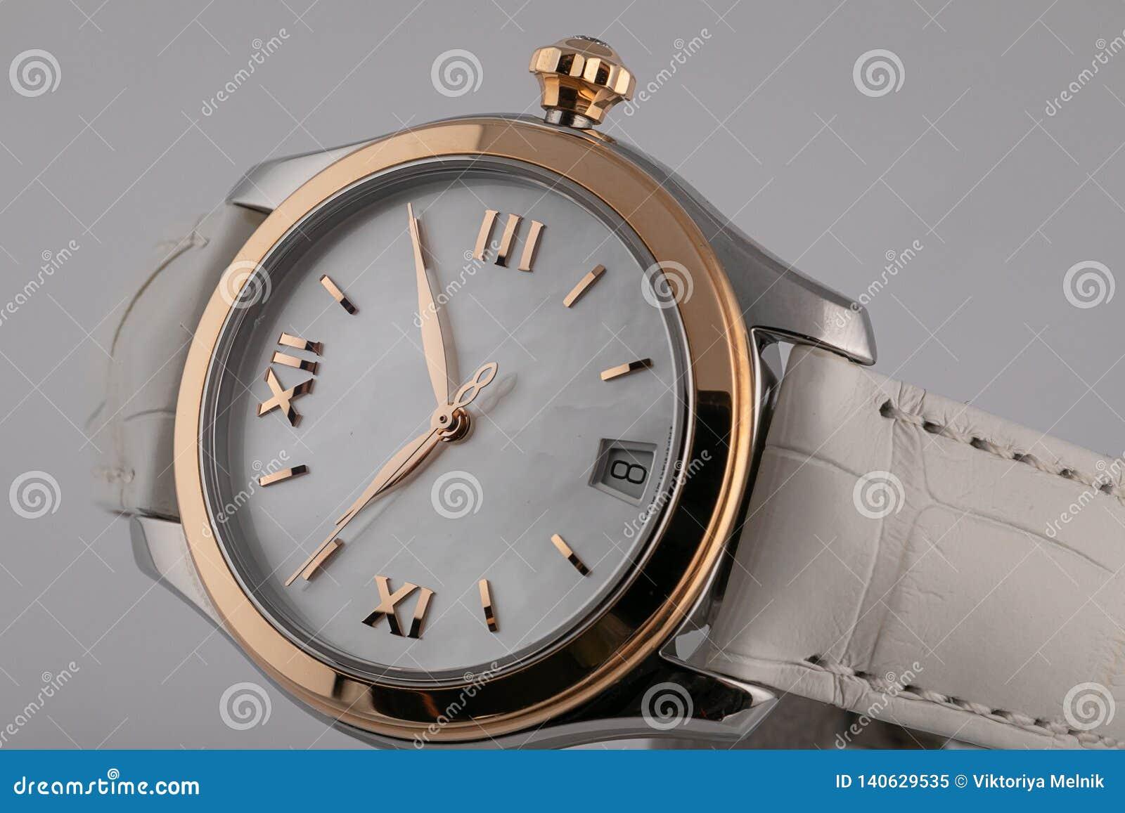有白革皮带、金边界、白色拨号盘,金子顺时针和罗马数字的妇女的手表隔绝在白色背景