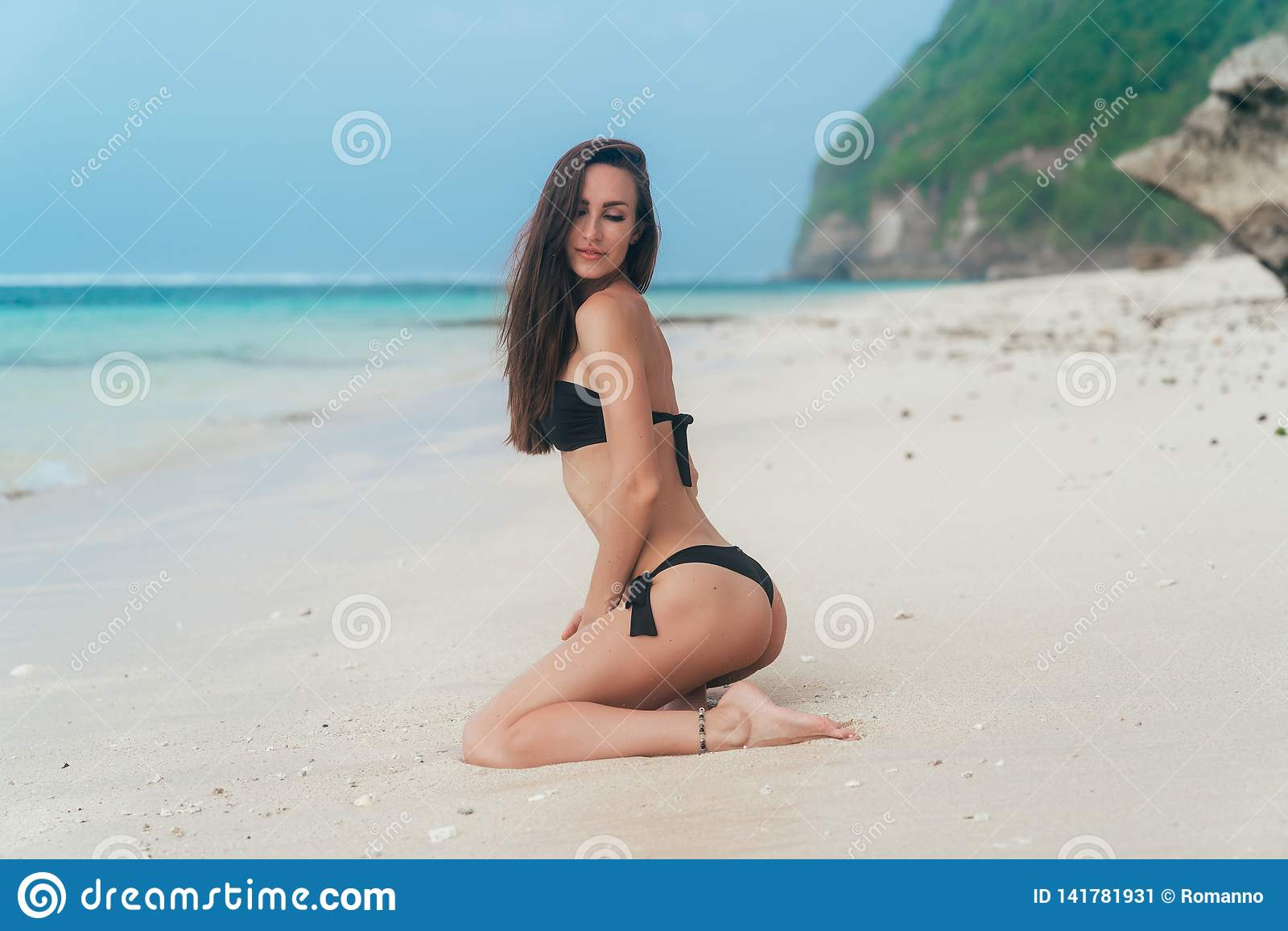 有运动的身体的性感女孩在海滩的黑比基尼泳装姿势与背景的蓝色海洋