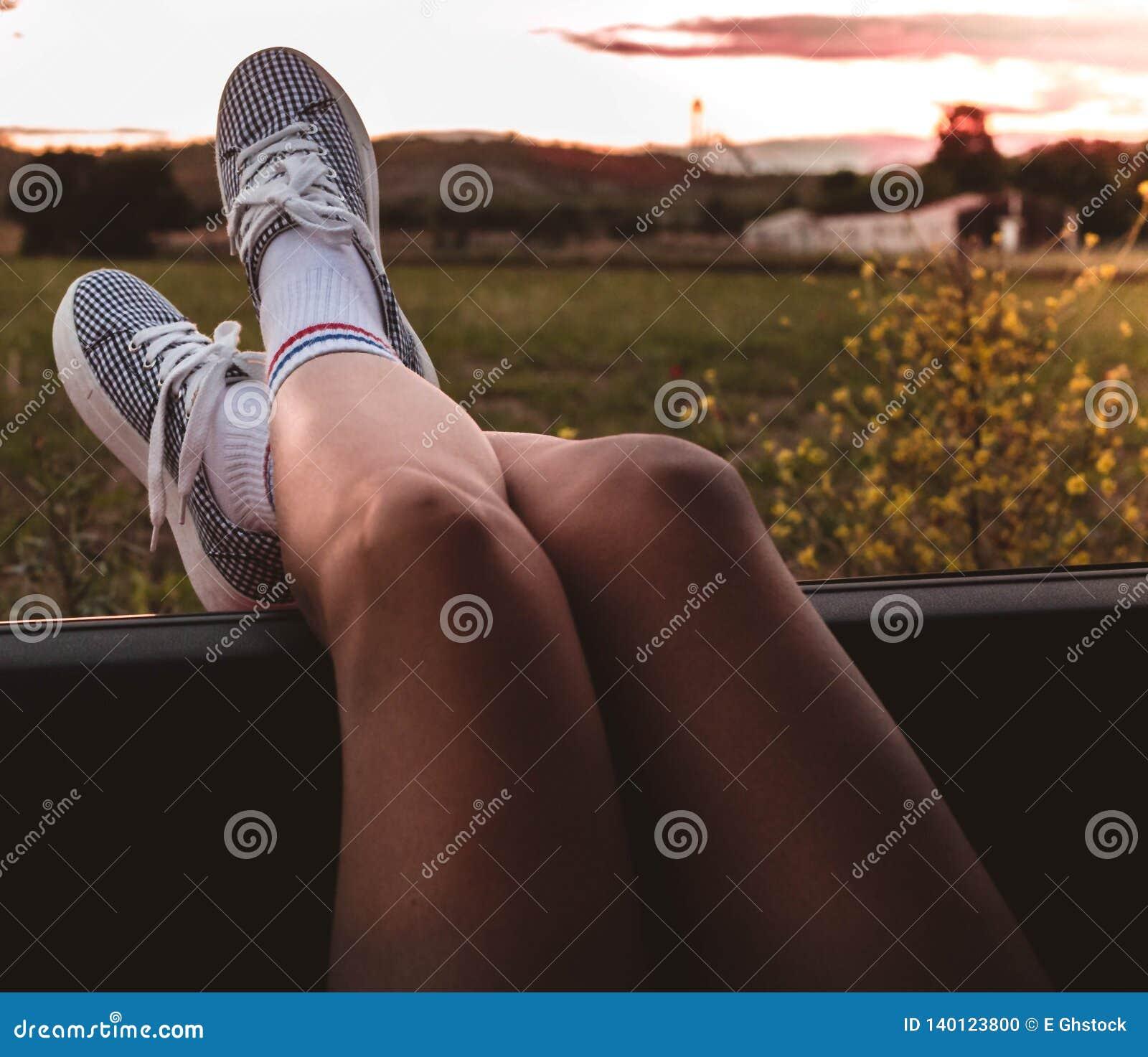 有运动鞋的年轻女人有在车窗扶植的脚的在日落