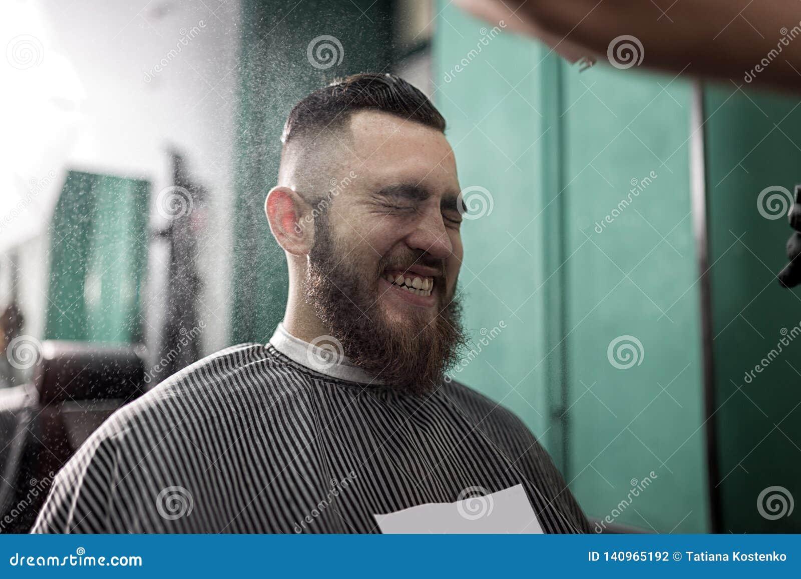 有胡子的时髦的人坐并且微笑在理发店 黑手套的理发师做喷洒发型的