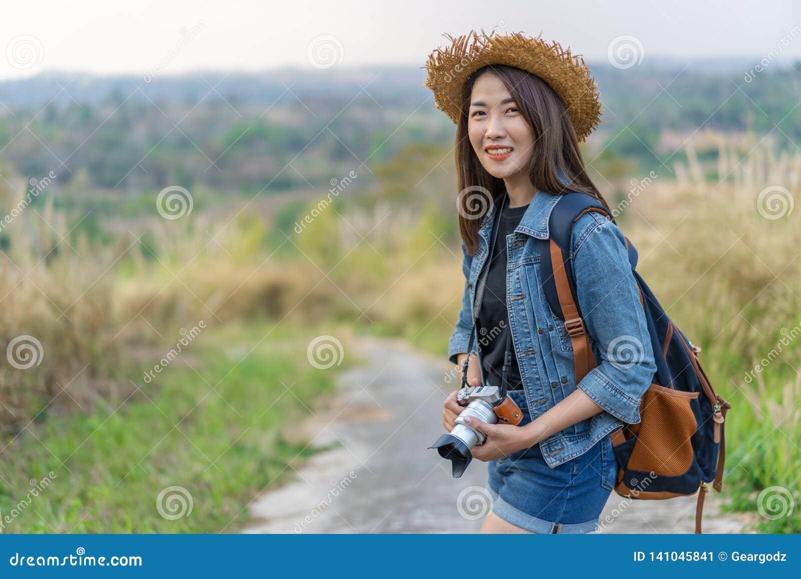 有背包的女性游人和照相机在乡下