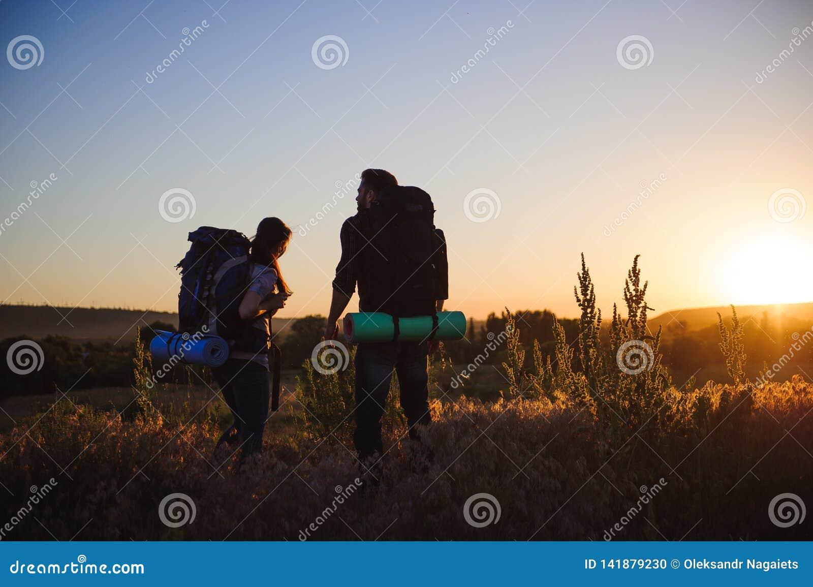 有背包的走在日落的两个远足者剪影 迁徙和享受日落视图