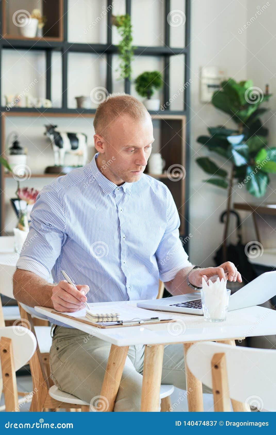 有膝上型计算机和纸的咖啡馆经理