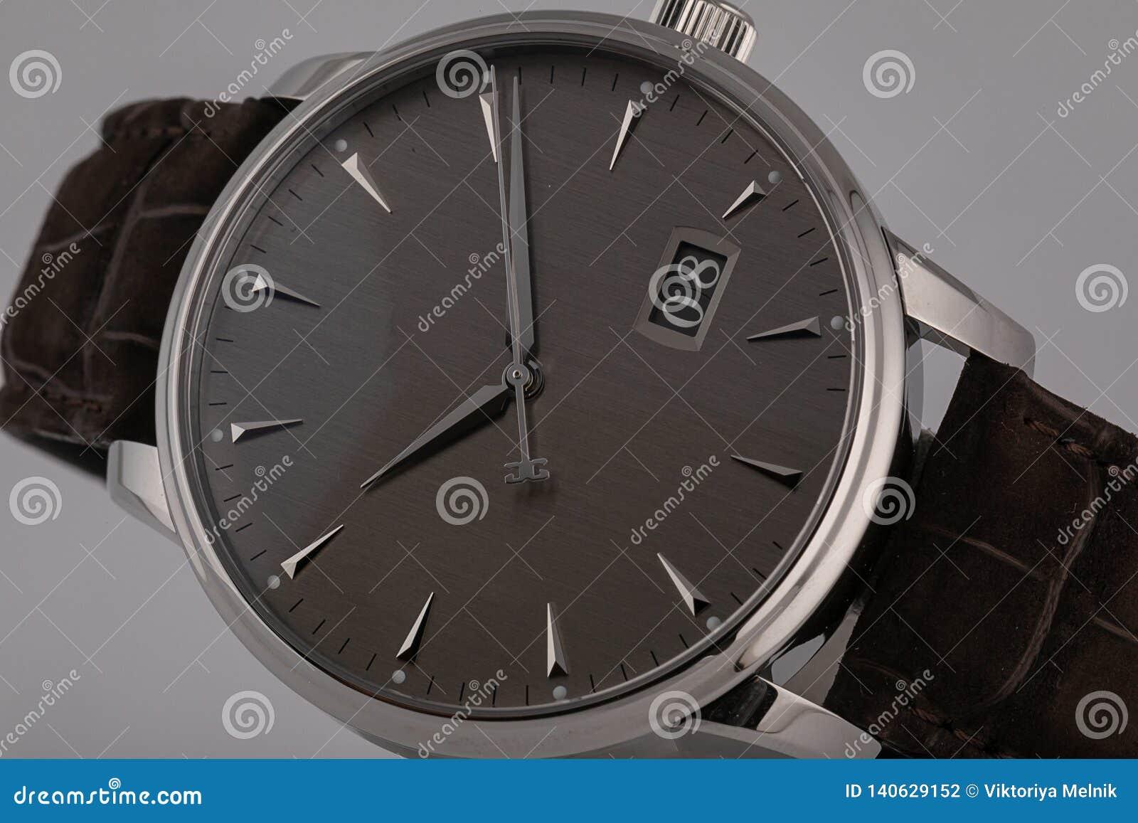 有顺时针方向棕色皮带的,灰色拨号盘人的手表,在银色身体,测时器,黑,数字隔绝在灰色背景