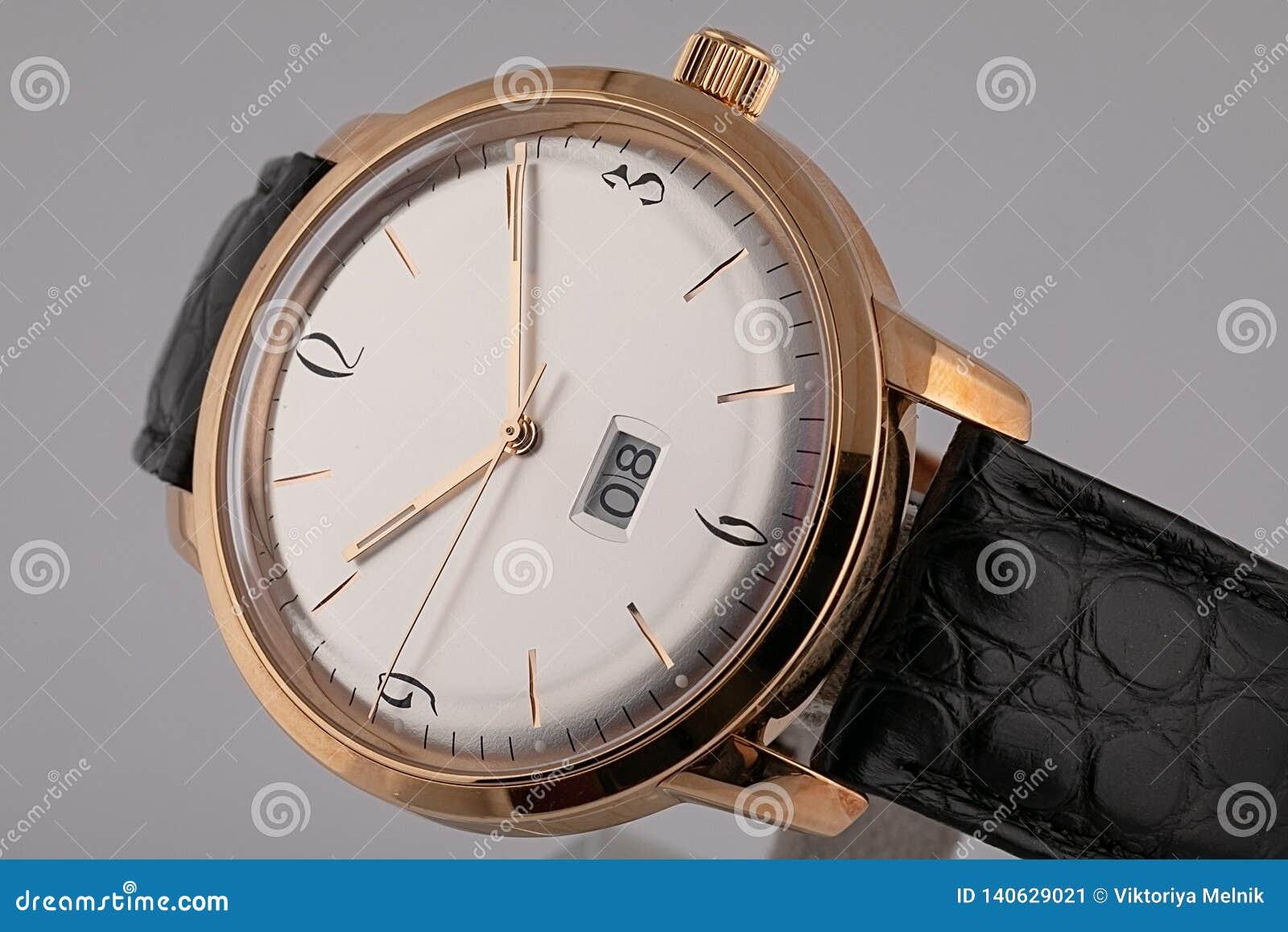 有顺时针方向黑皮带的,白色拨号盘人的手表,在金黄身体,测时器,金黄,数字隔绝在灰色背景