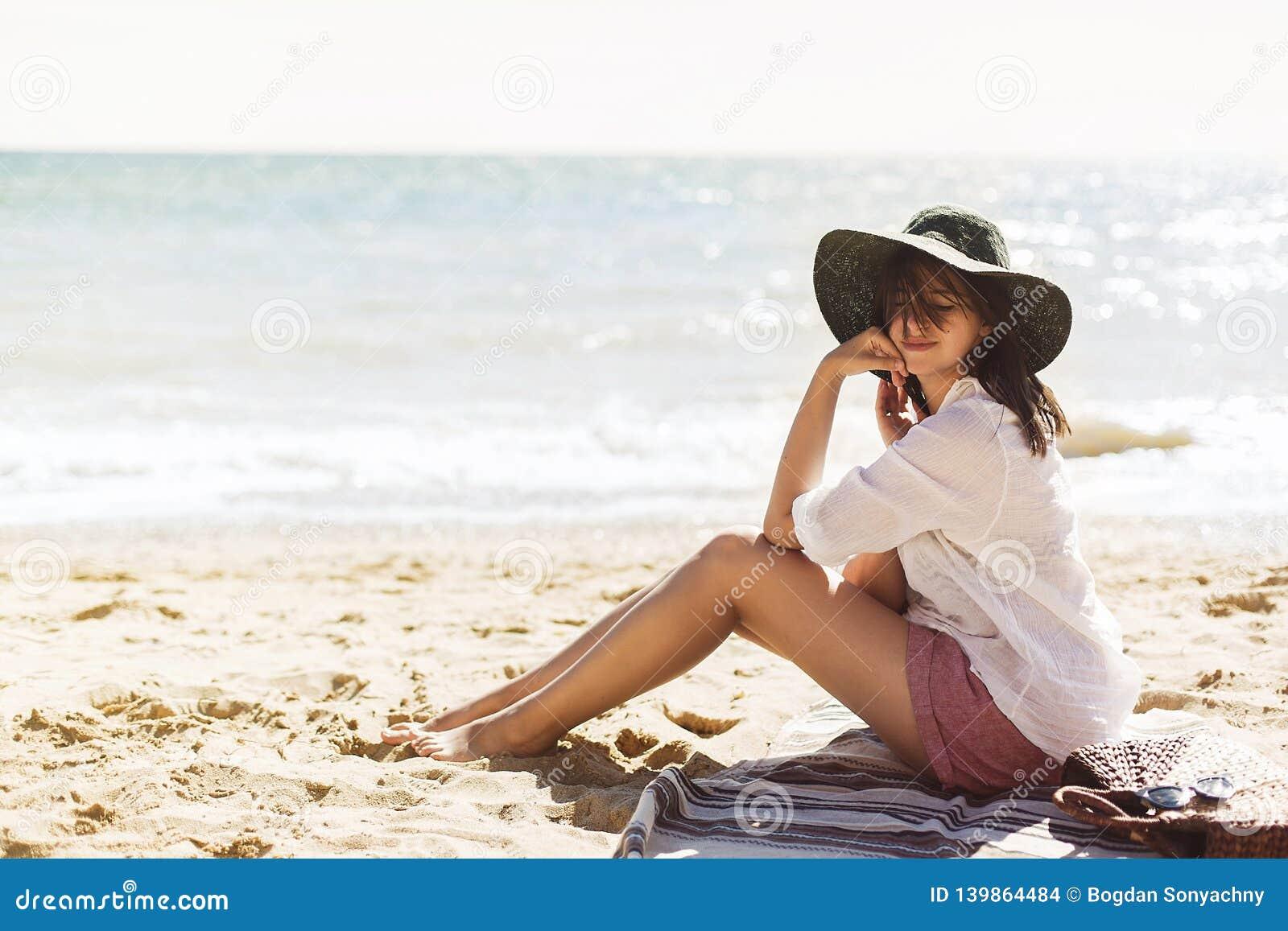 暑假概念 放松在海滩的愉快的少妇 晒黑的白色衬衫和的帽子的行家亭亭玉立的女孩坐和